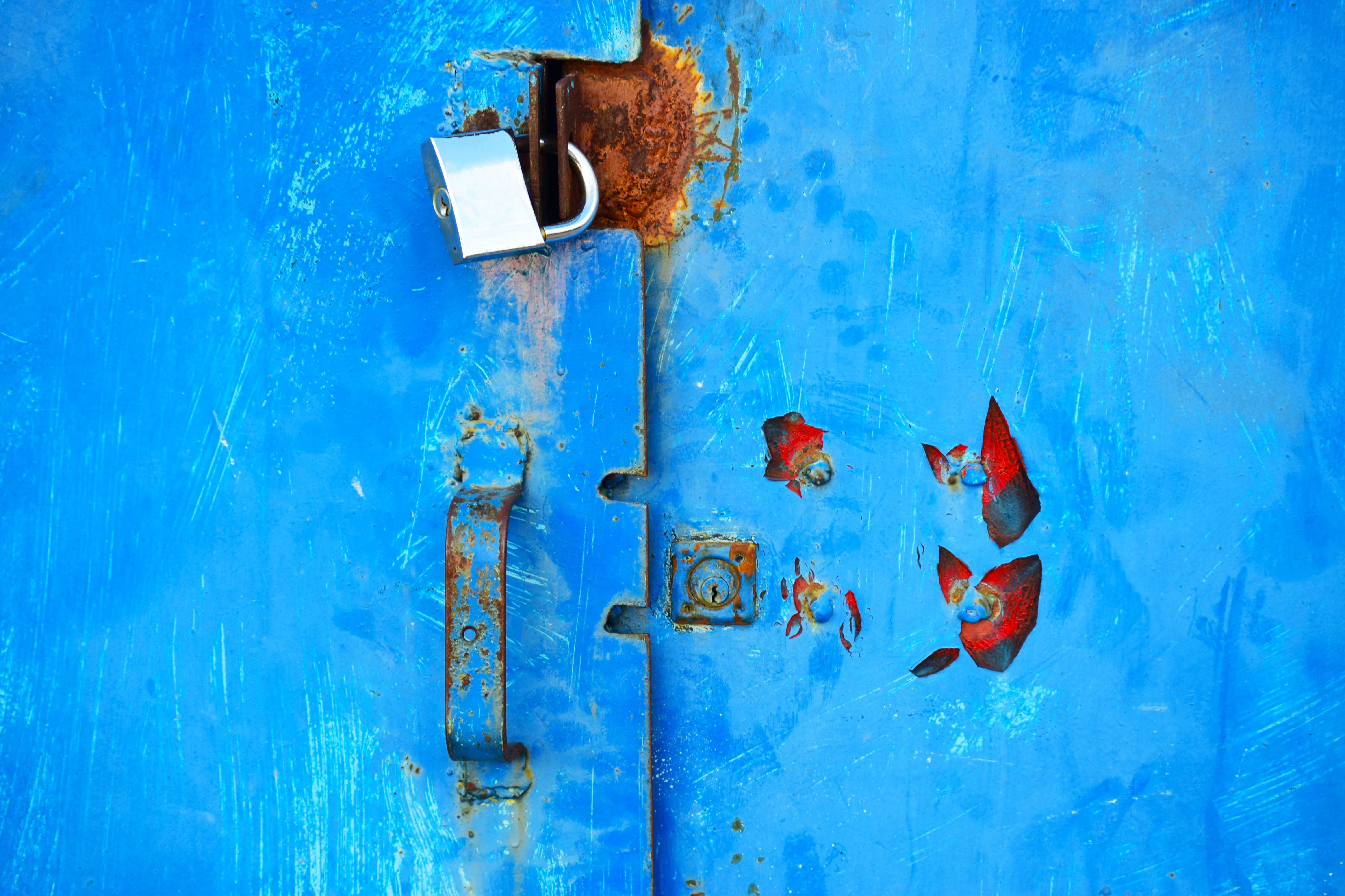 silver padlock on blue steel door