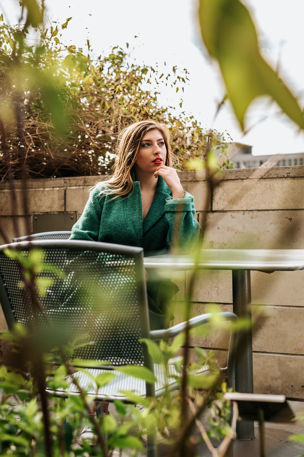 woman sitting on armchair outside during daytime