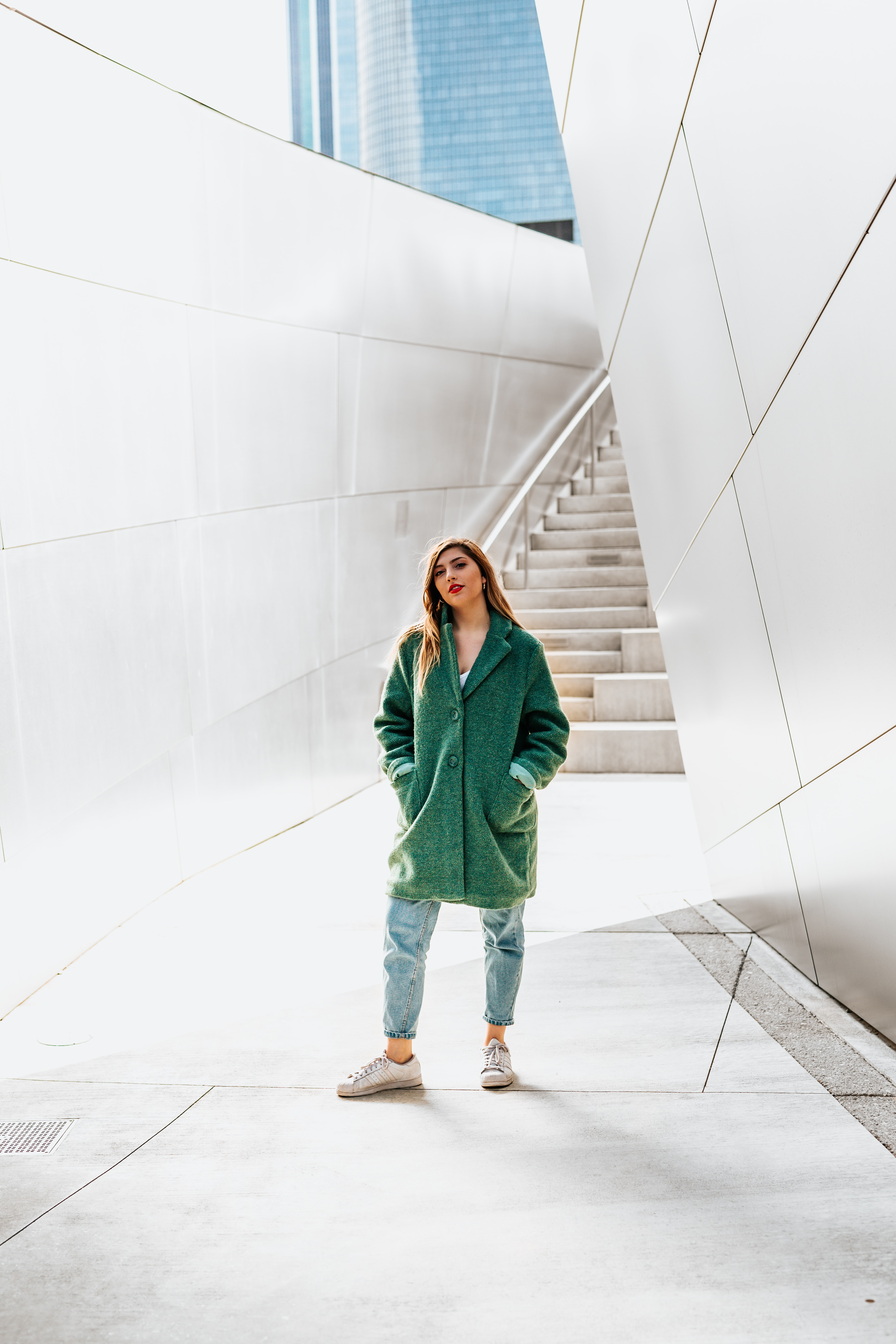 woman standing near wall while hands in jacket pockets