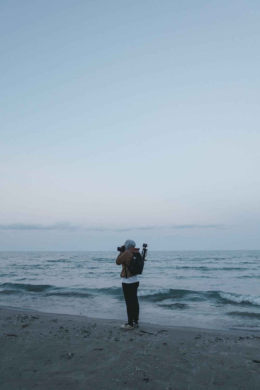 woman taking a photo of sea