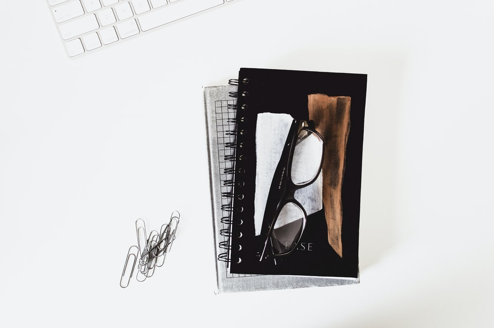 eyeglasses with black frames on book