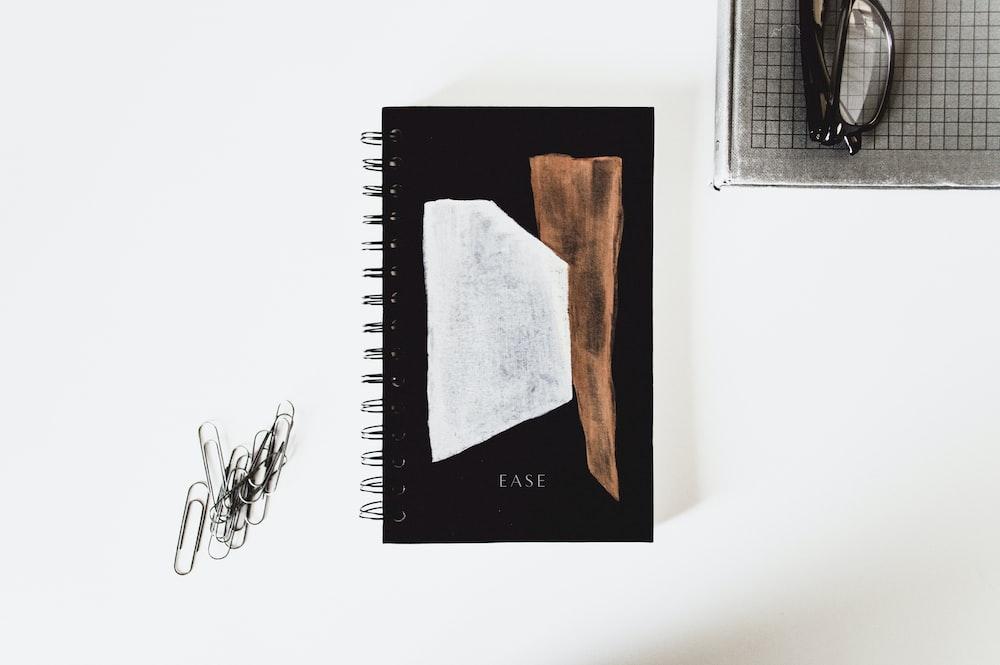 closed notebook near eyeglasses