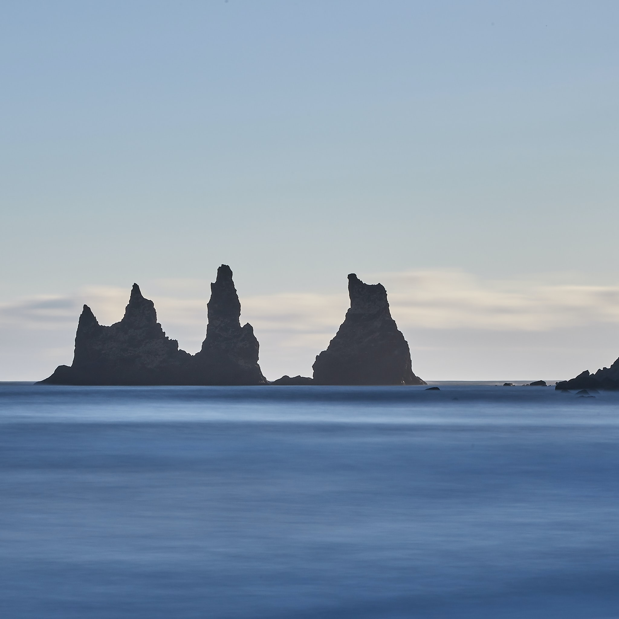 silhouette of rock formation on sea