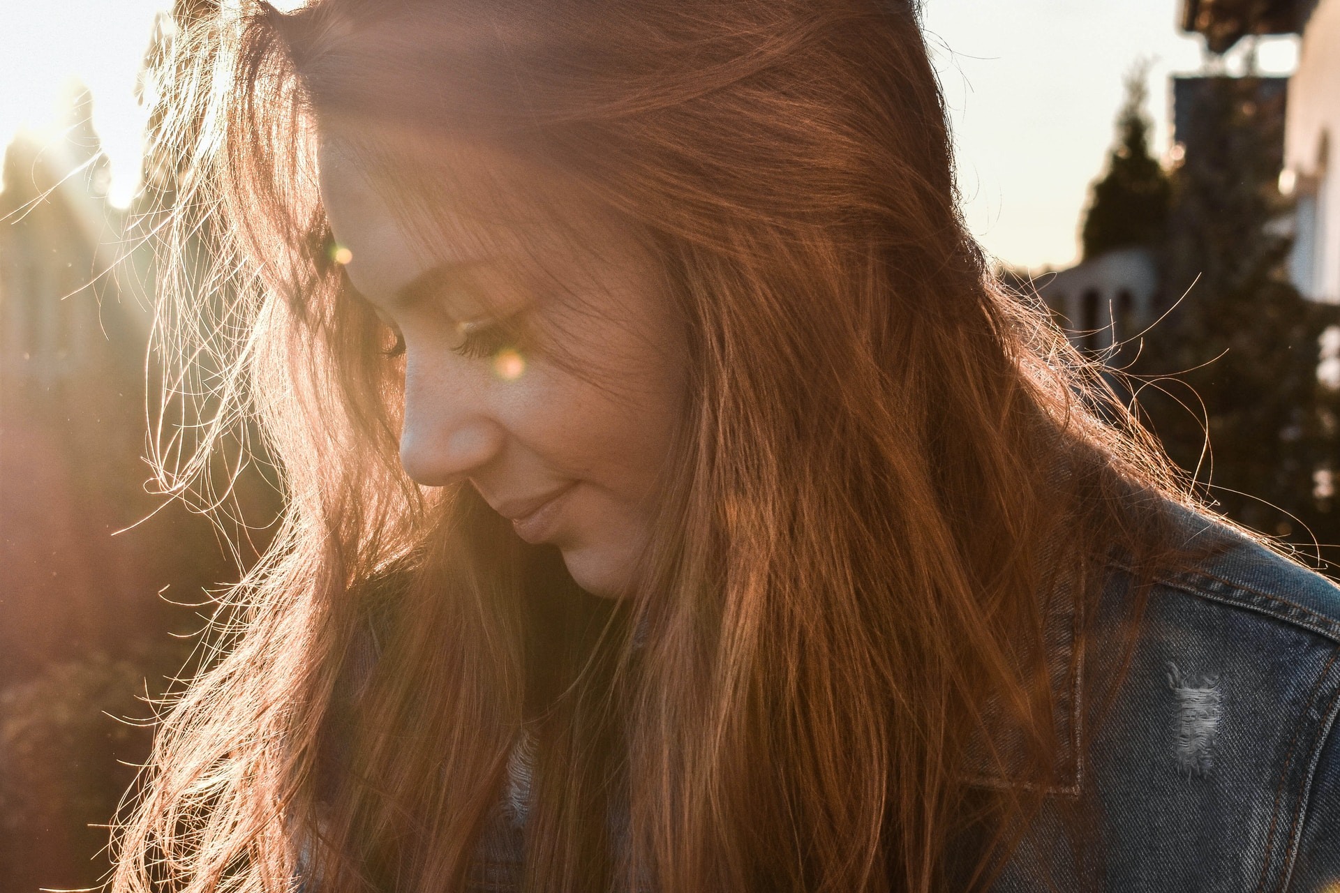 woman wearing blue denim jacket looking on her right side in shallow focus photography