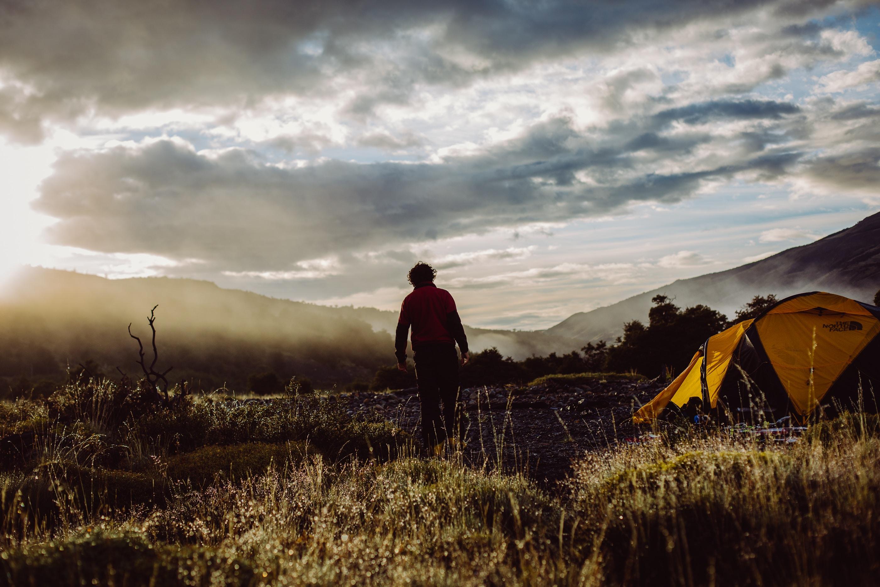 person walking near tent on green field