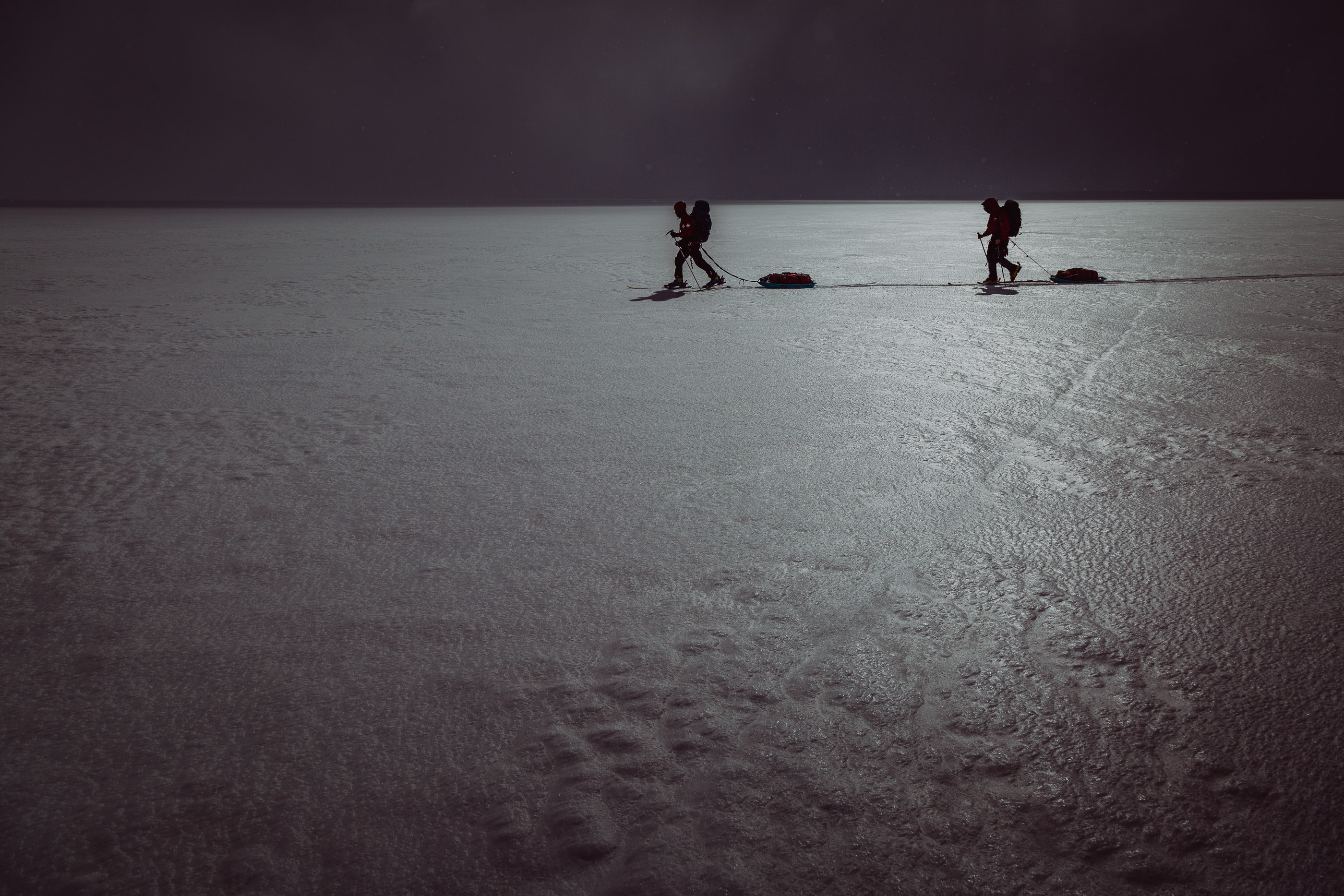 two person walking on snowfield
