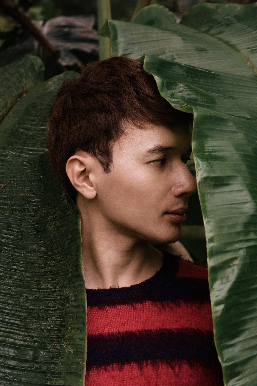 man standing under leaves