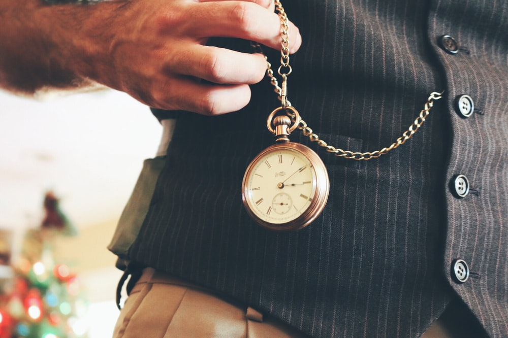 person holding round gold-colored pocket watch