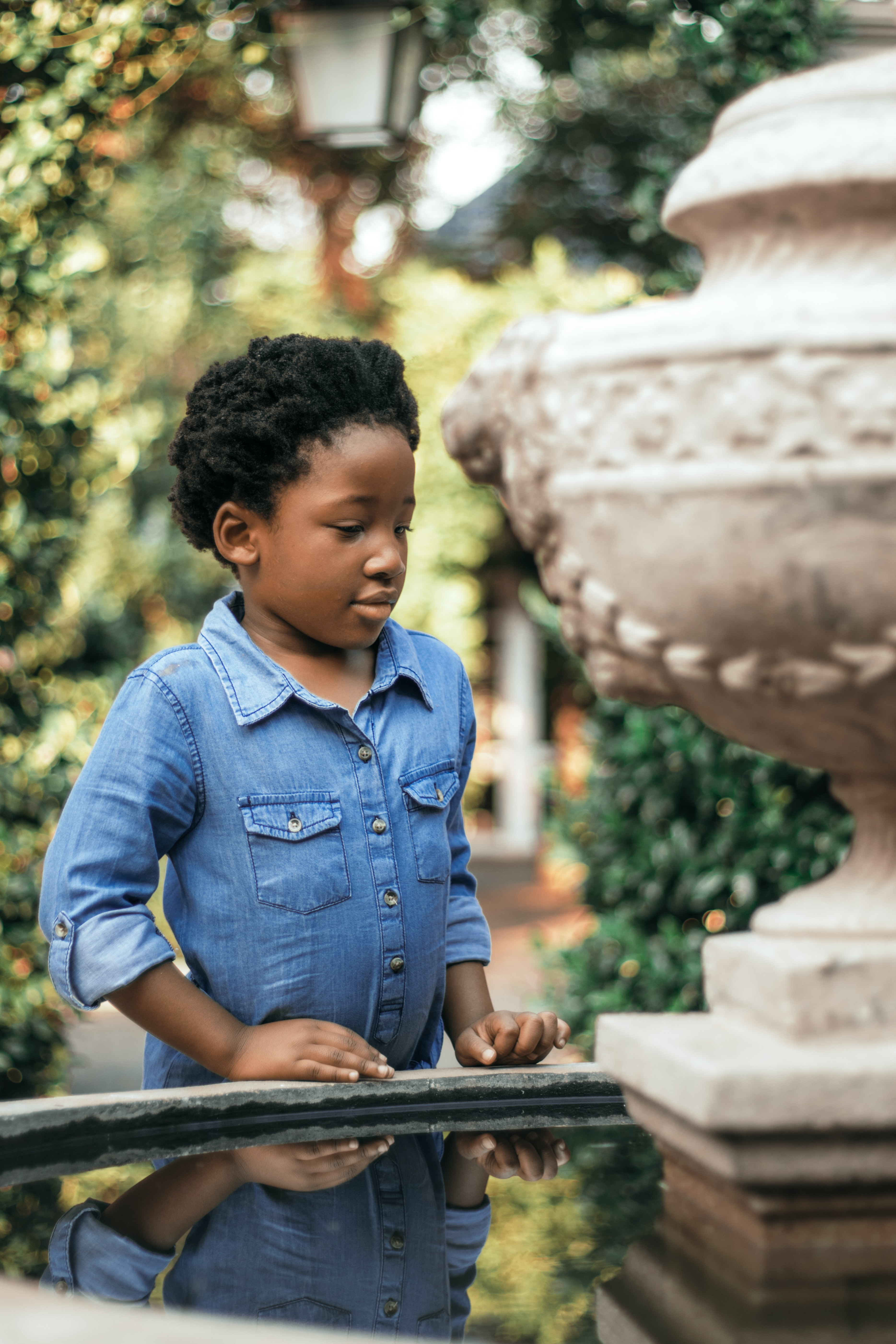 boy staring at the fountain during daytime