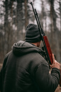 man holding brown and black sniper rifle in shallow focus photography