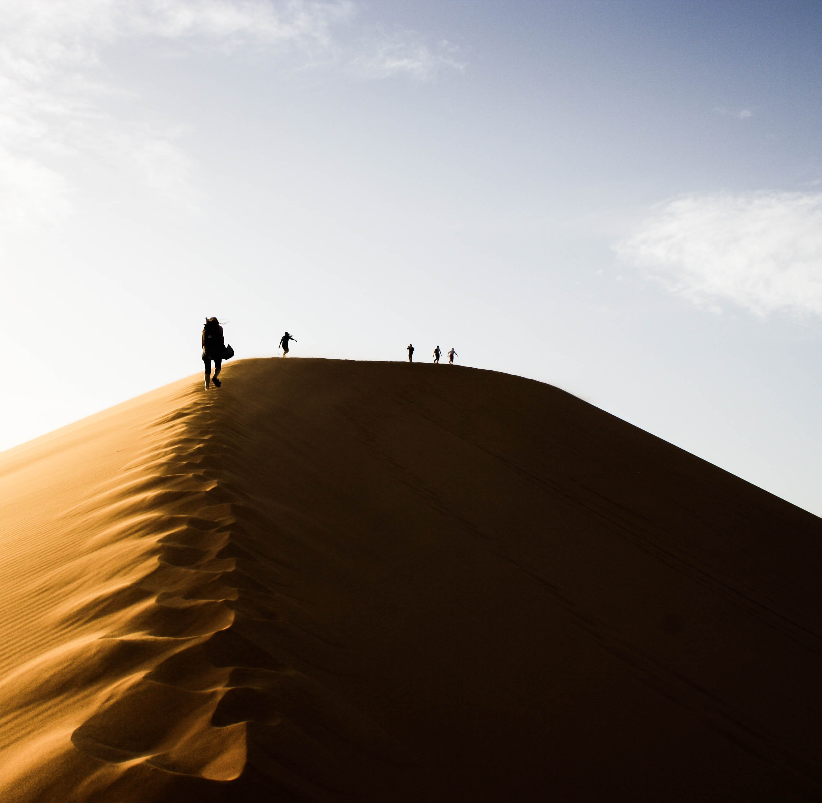 five people standing on sand dunes during daytime