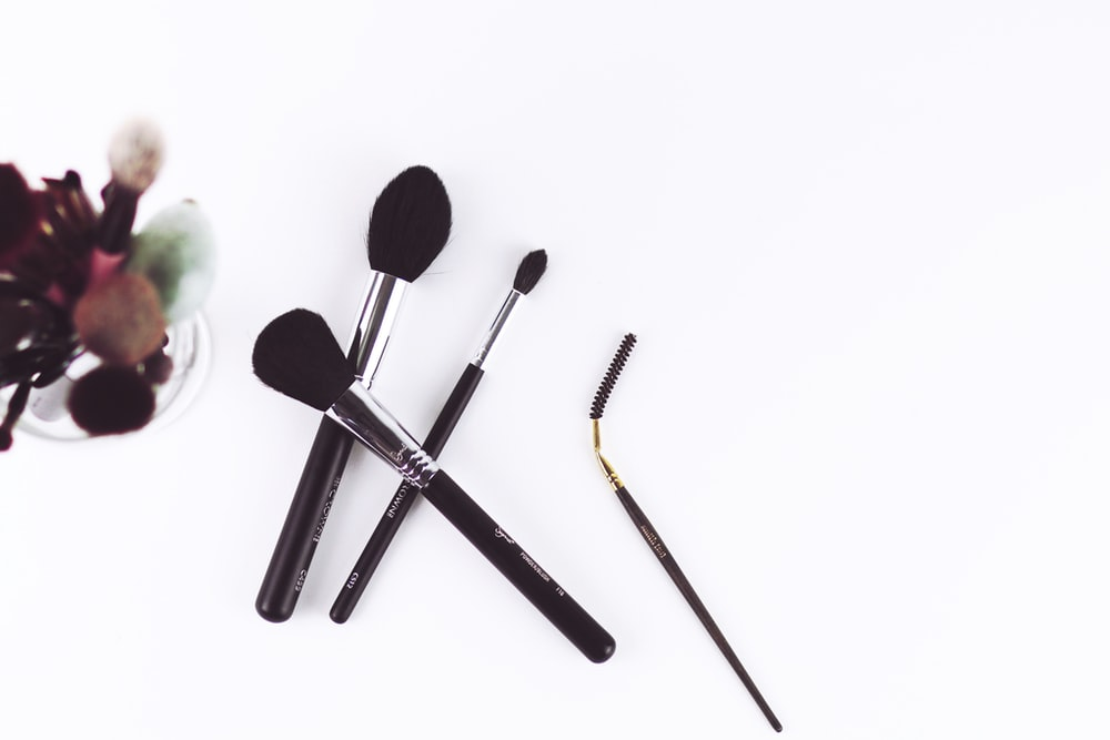 four black make-up brushes