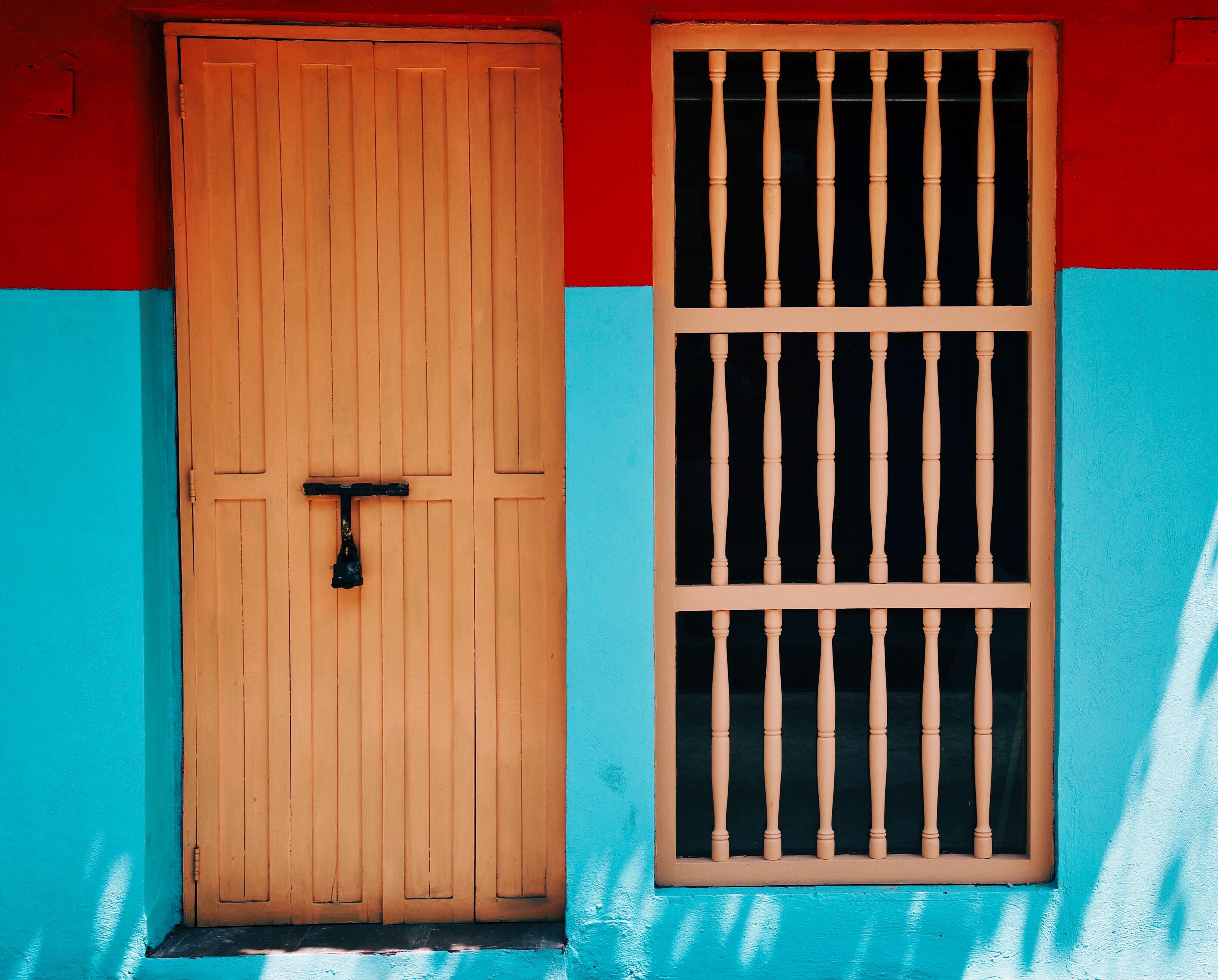 closed brown wooden door beside window