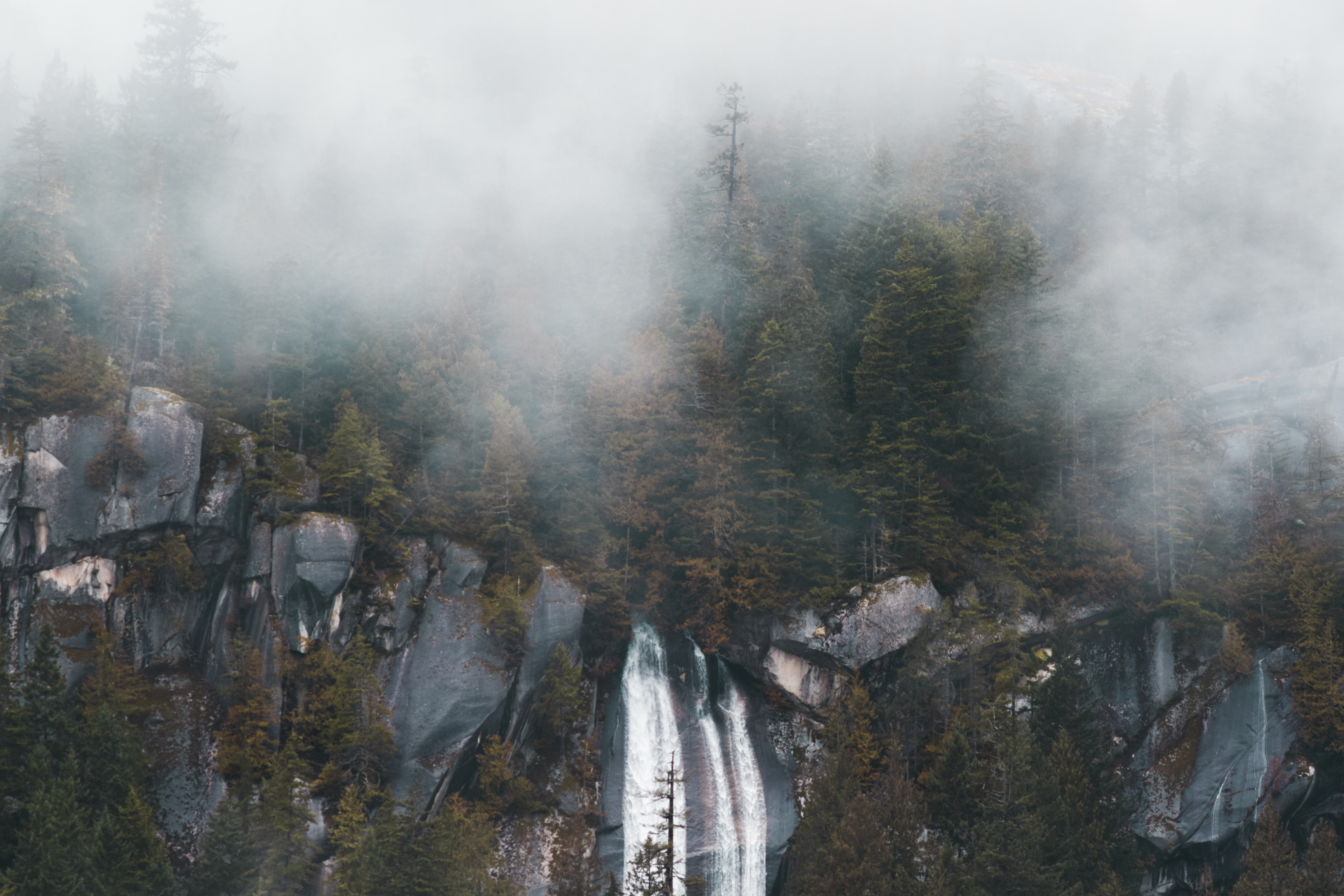 waterfalls beside green trees with cloudy sky