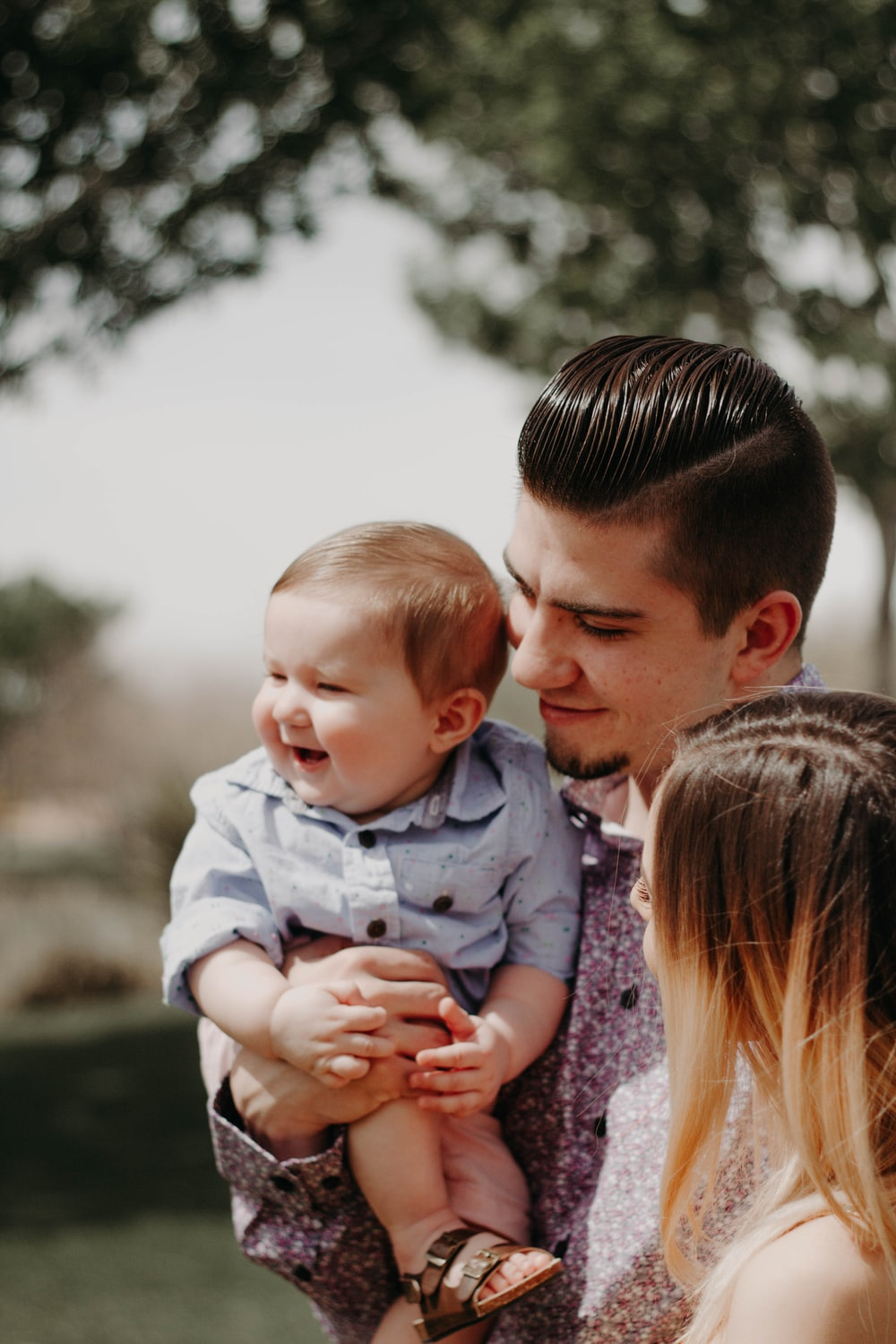 man carrying baby beside woman while smiling to each other
