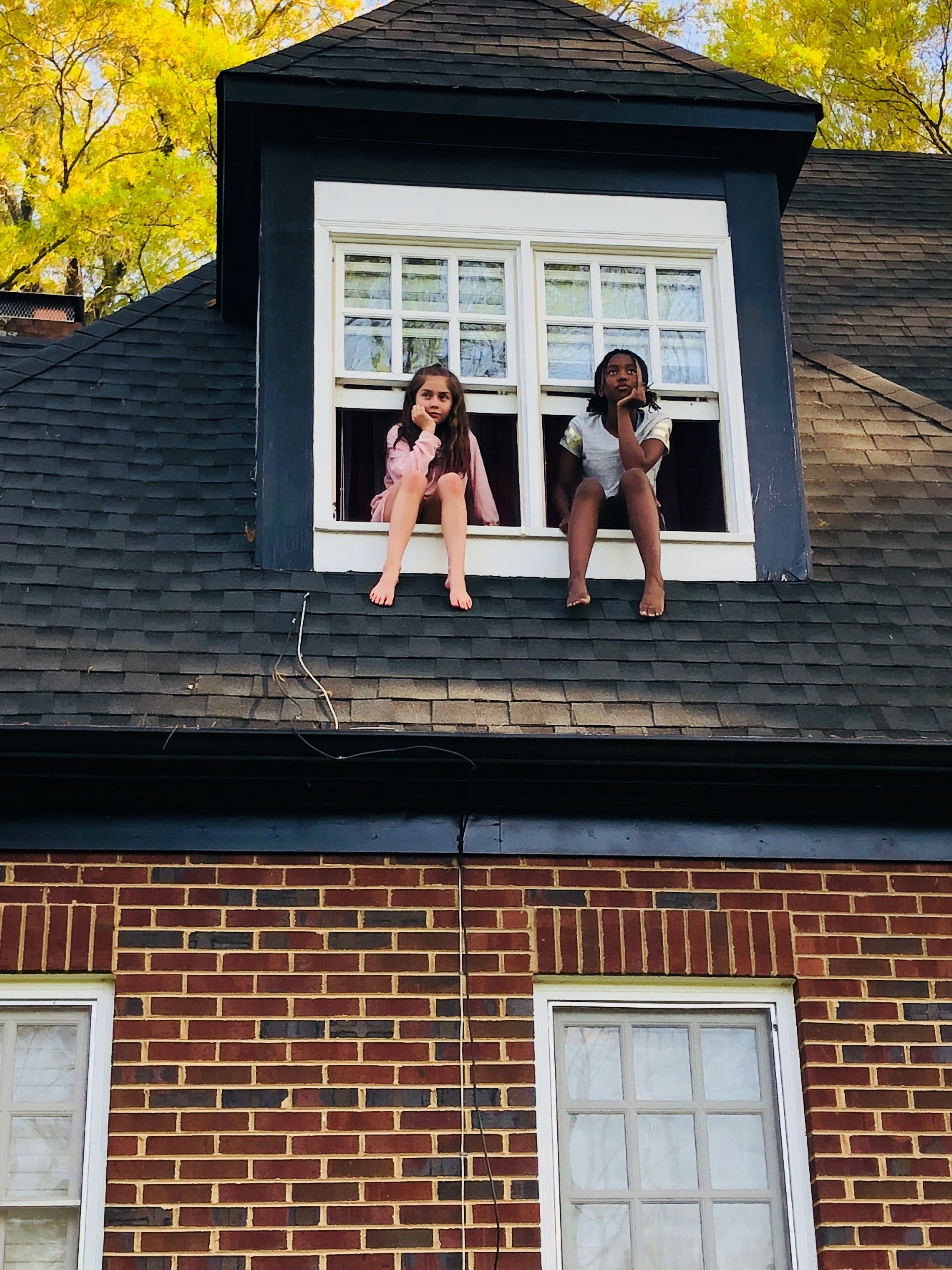 two girls sitting on white 2-panel windows during daytime