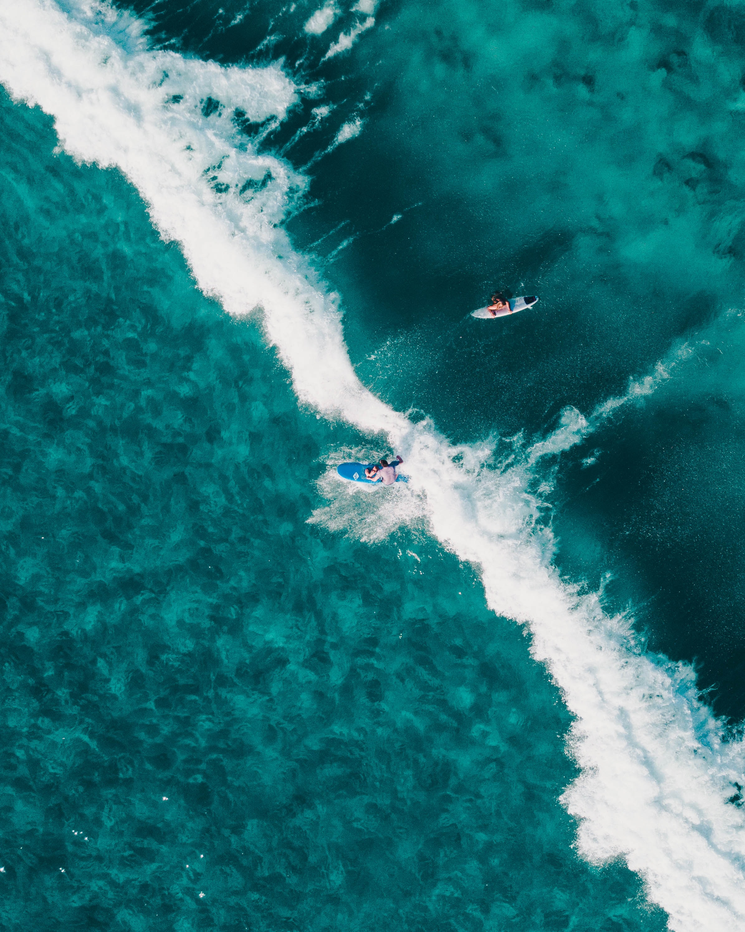 aerial view photo of two people surfing in body of water