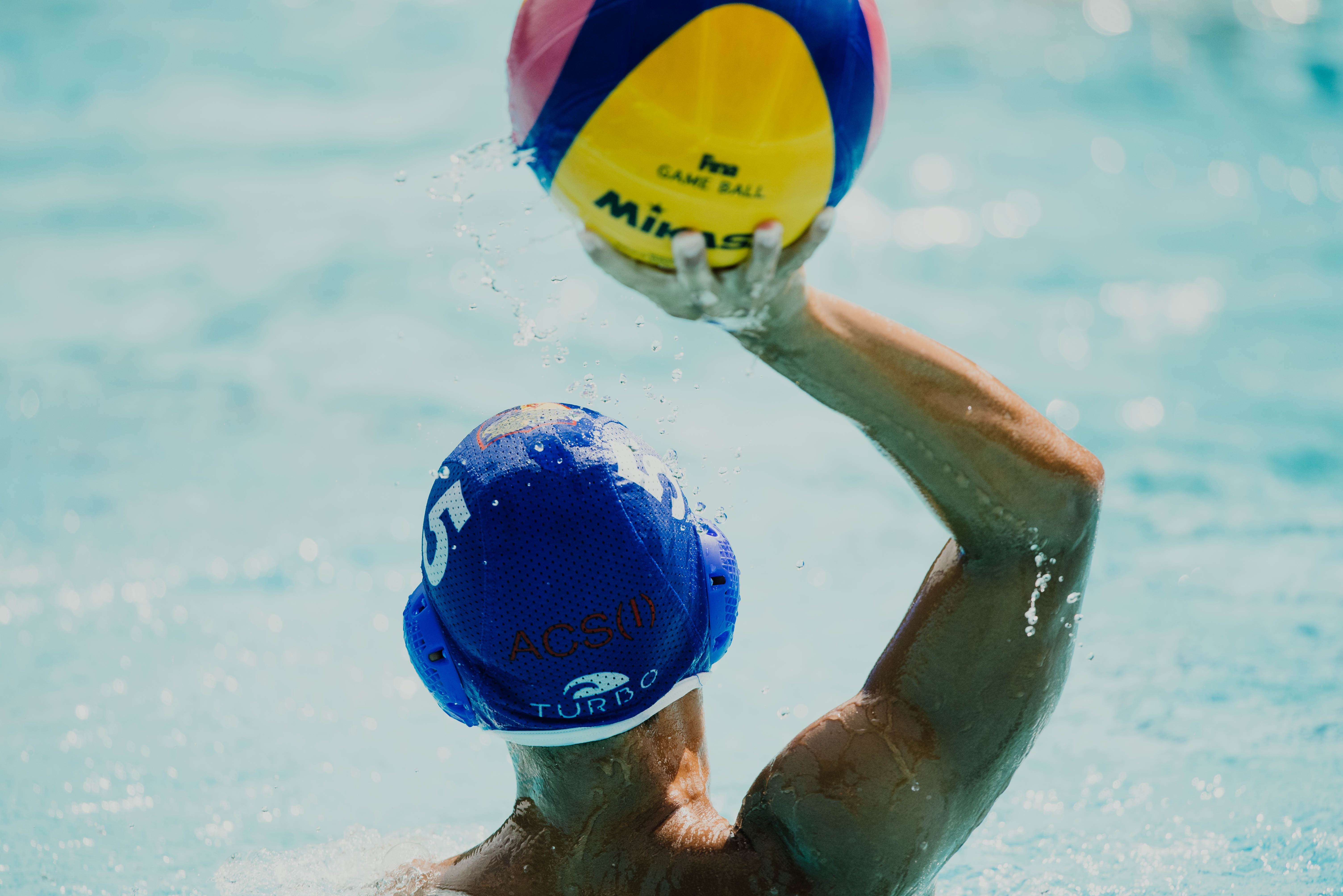 man throwing yellow, blue, and red Mikasa ball