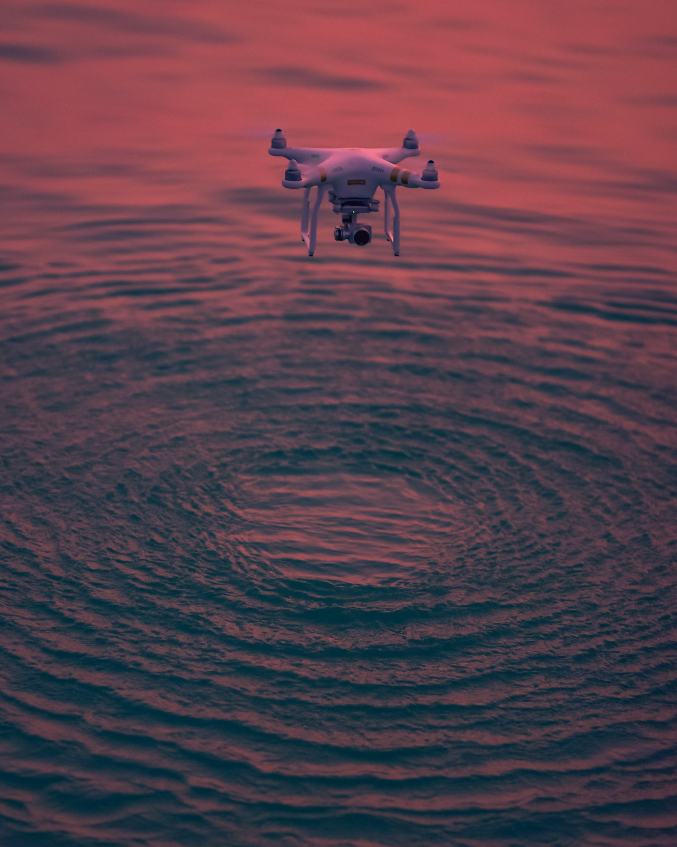yellow DJI Phantom Pro above water during golden hour