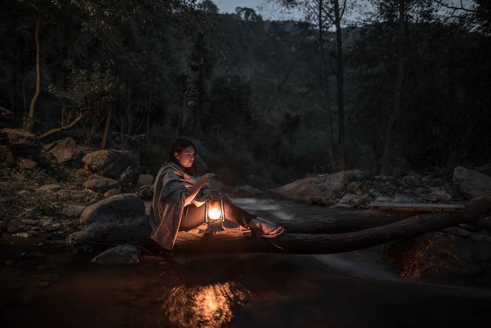 Woman Sitting On Log Carrying Kerosene Lamp