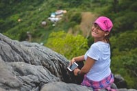 woman sitting on rock cliff near trees at daytime