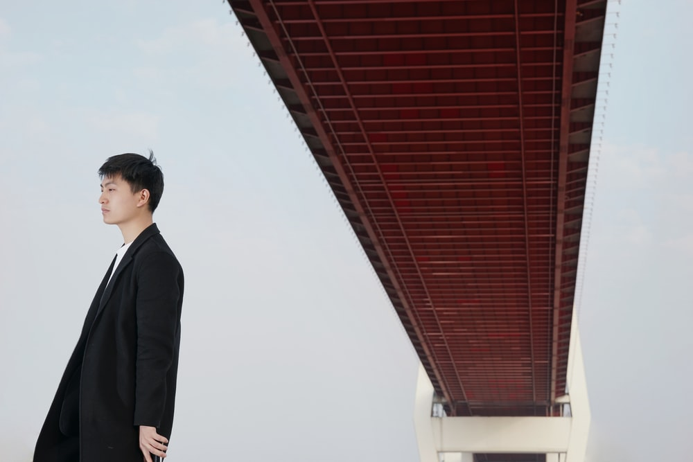 man standing under brown bridge