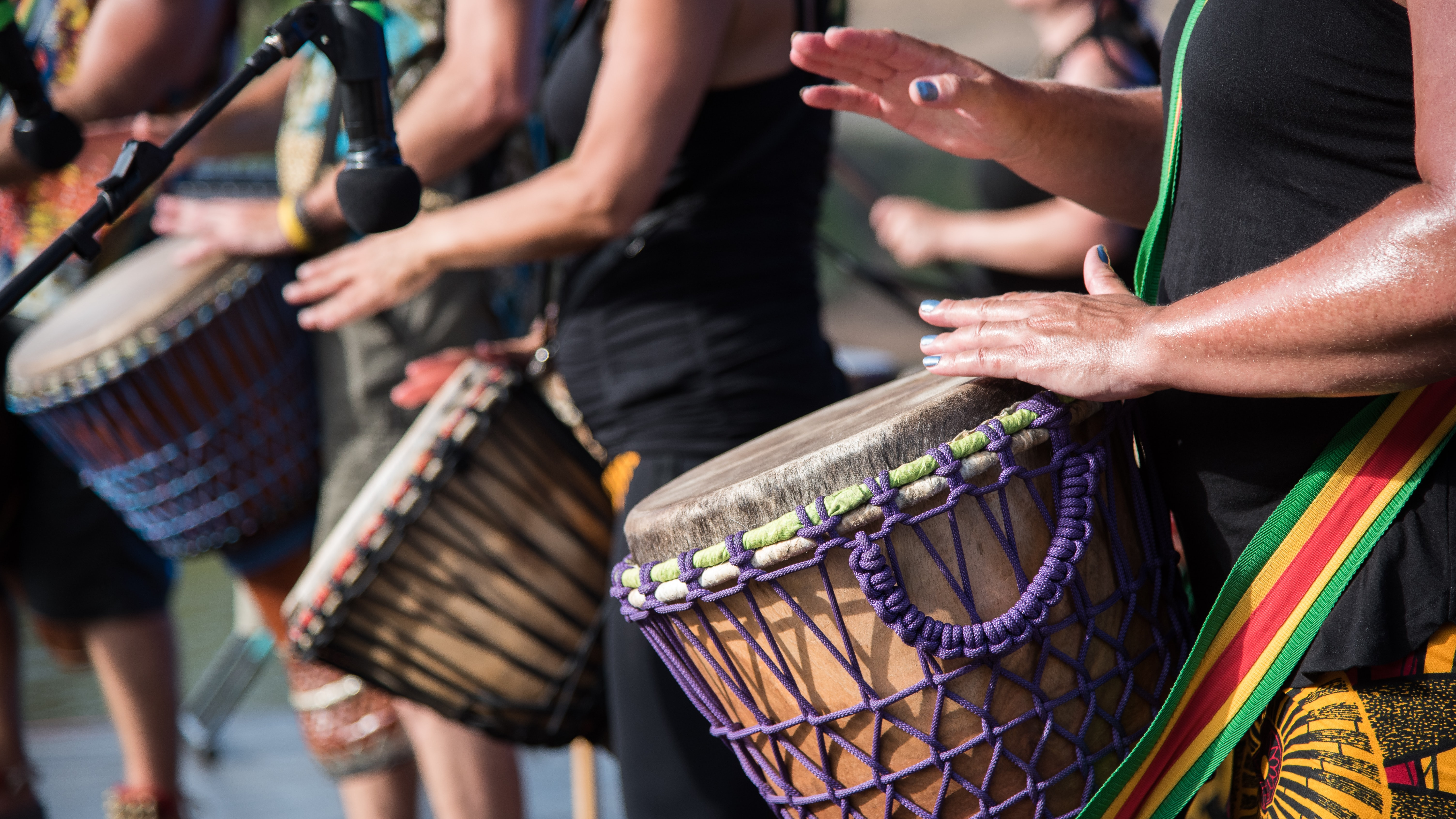 people playing goblet drums during daytime