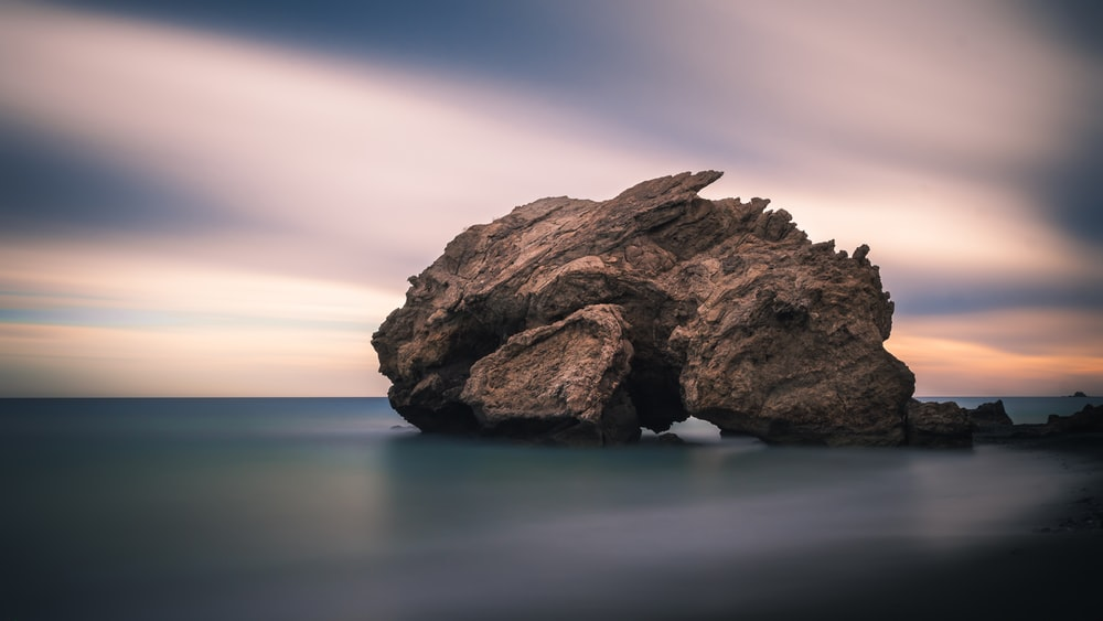 rock formation on body of water under golden hour