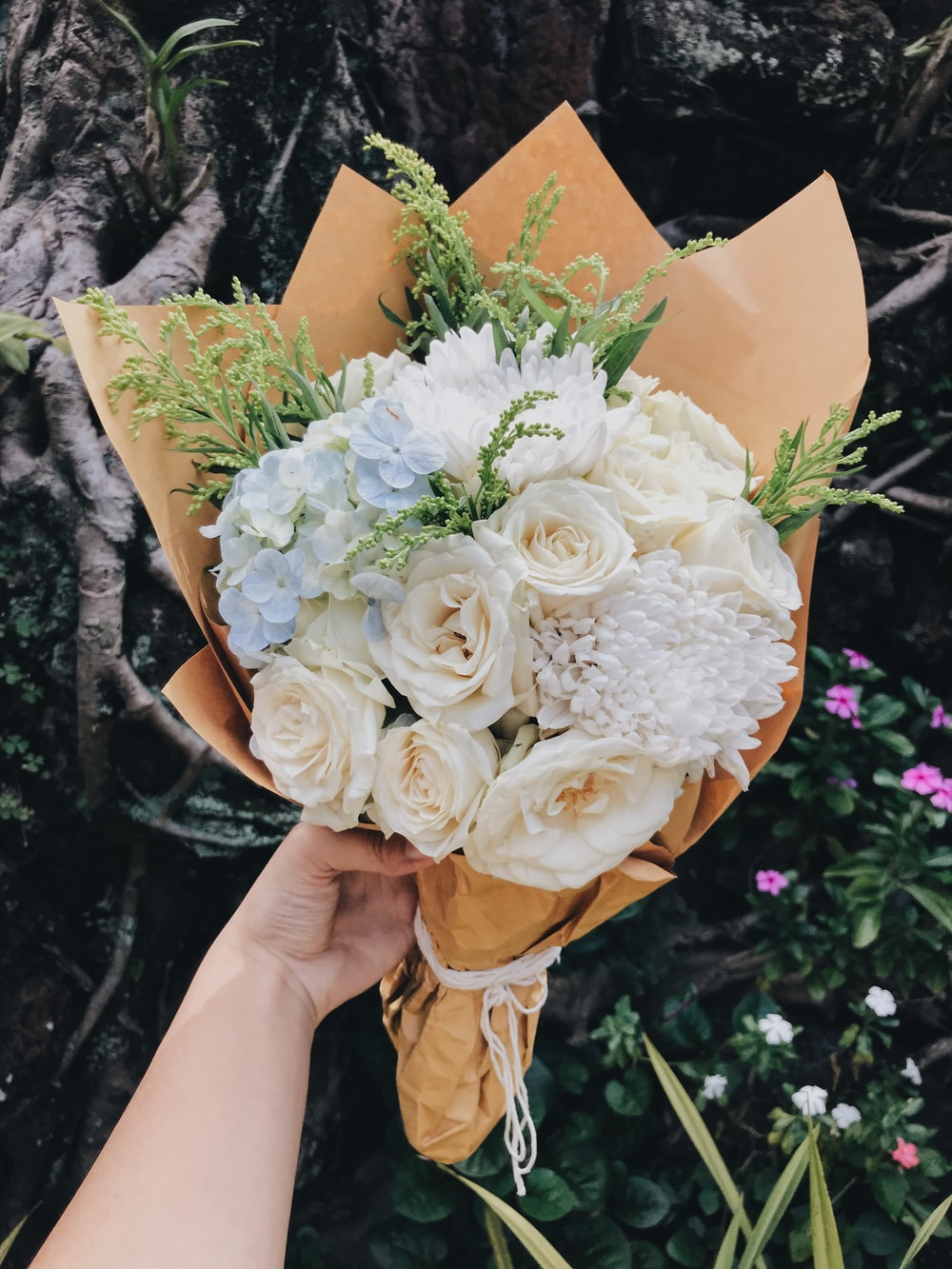 person holding beige and white flower bouquet