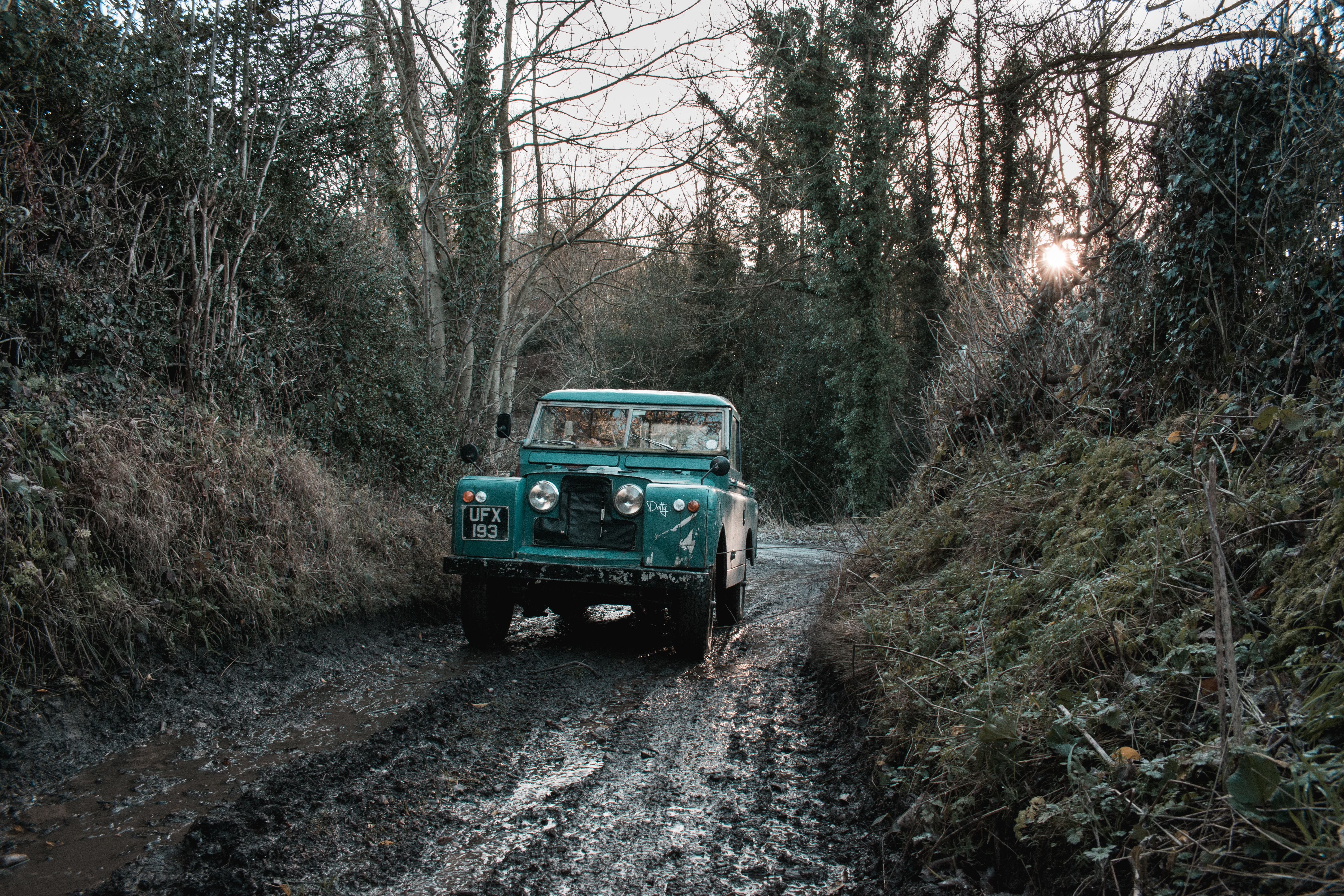 green car on rough road during daytime