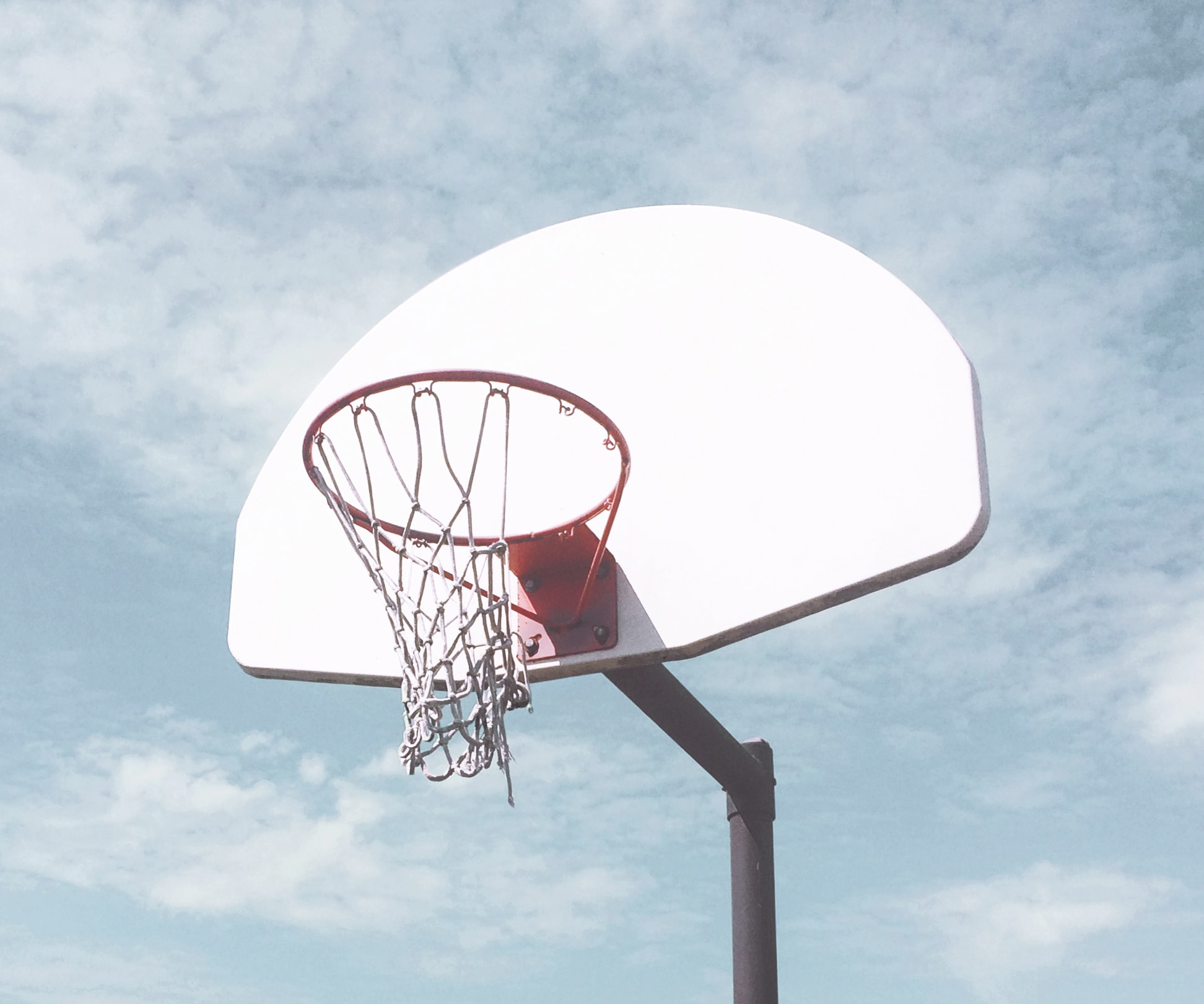 low-angle photography of basketball ring under cloudy sky