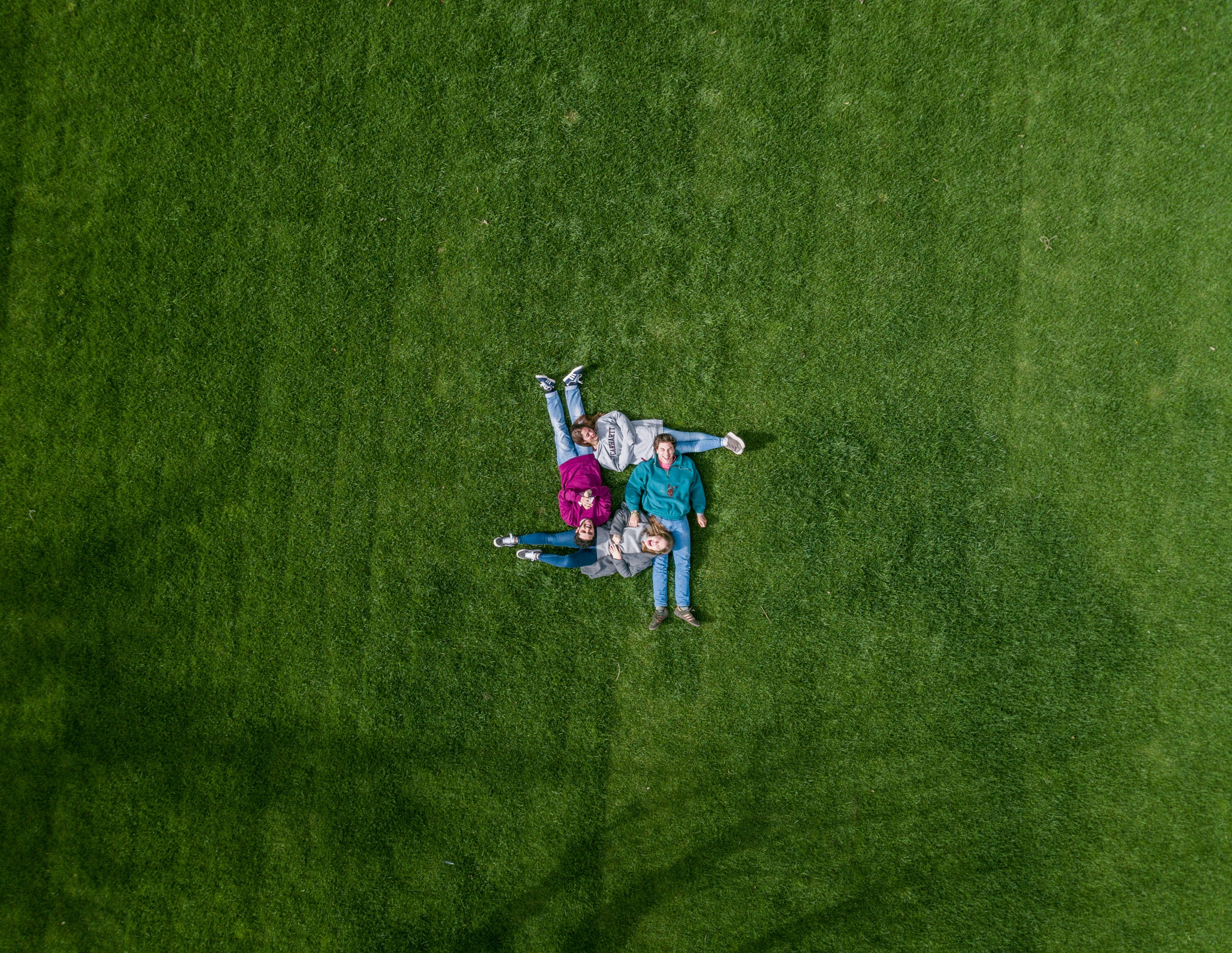 four people on green field at daytime