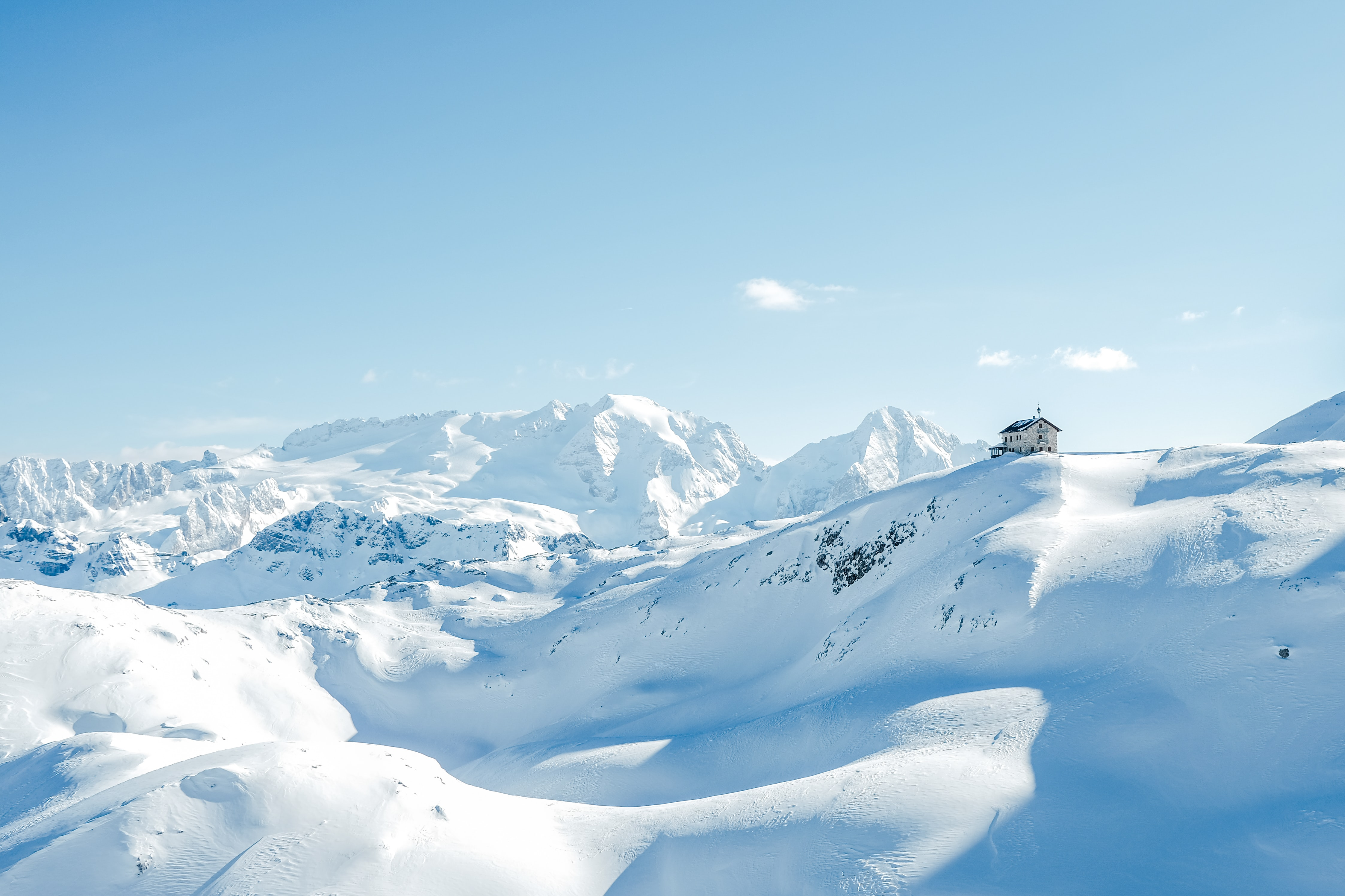 house on top of snow covered hills and mountains during day