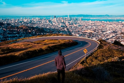 man standing near road looking at city buildings san francisco zoom background