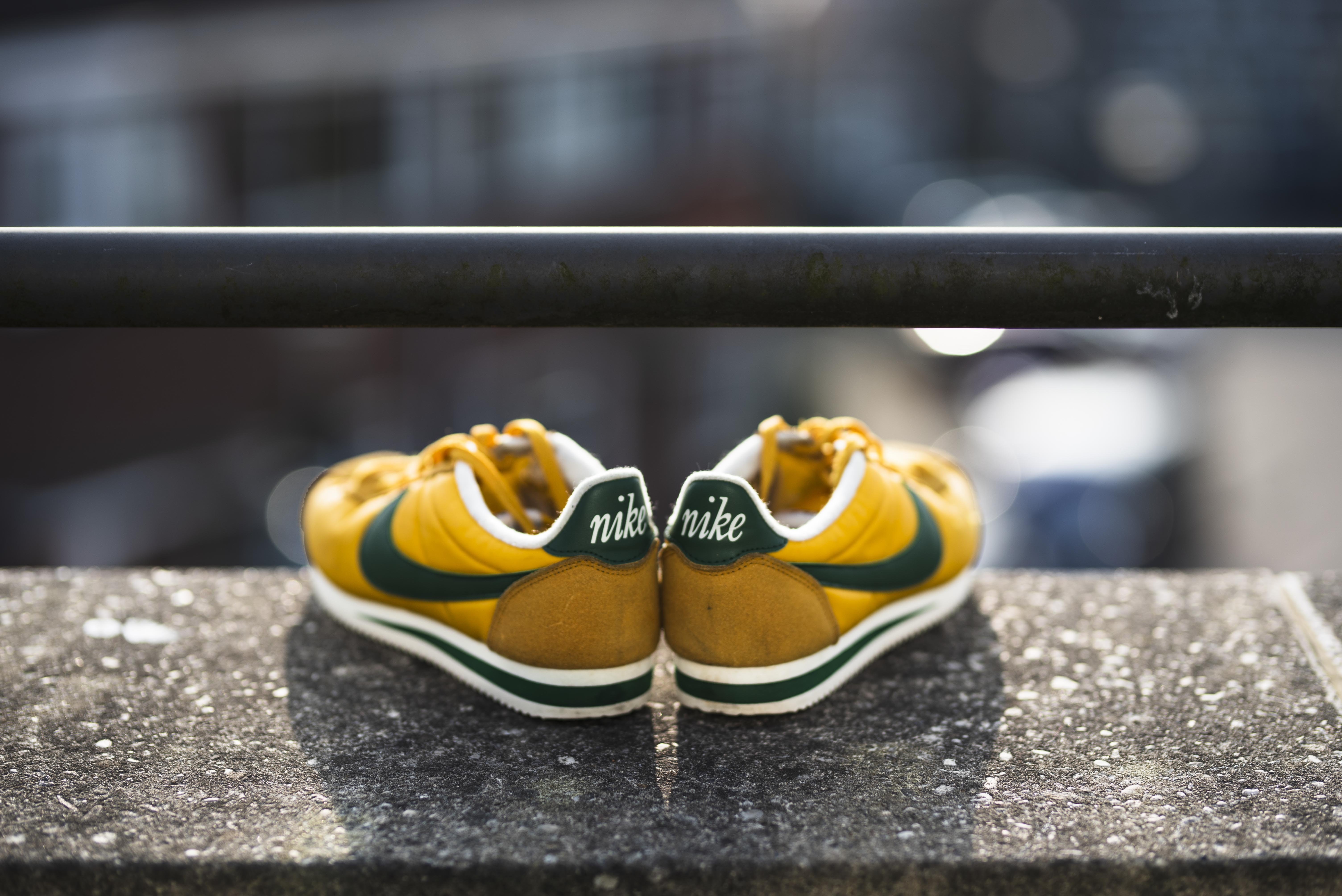 selective focus photography of yellow-black-and-white Nike Cortez shoes