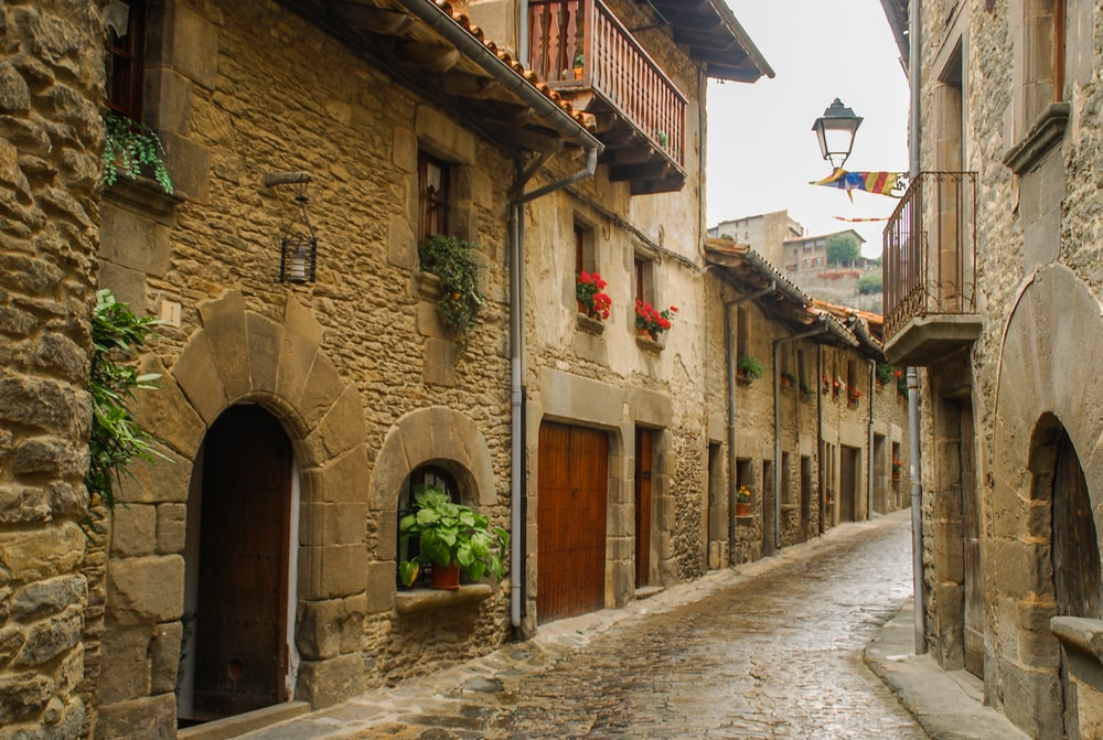 narrow road between concrete brick houses