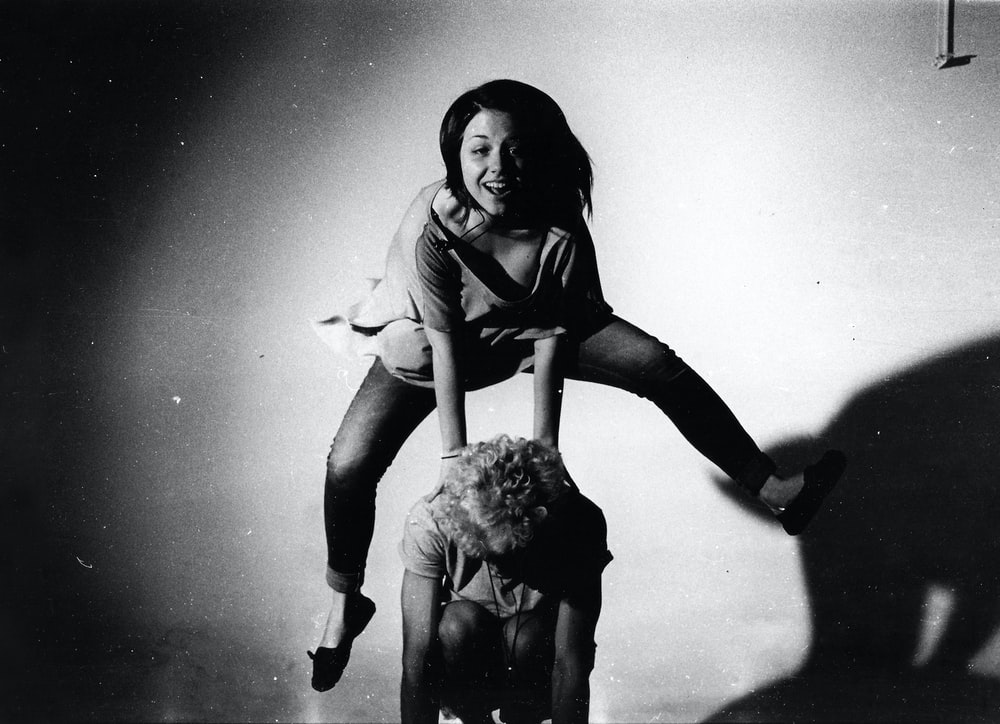 woman jumping on other person's back in grayscale photography