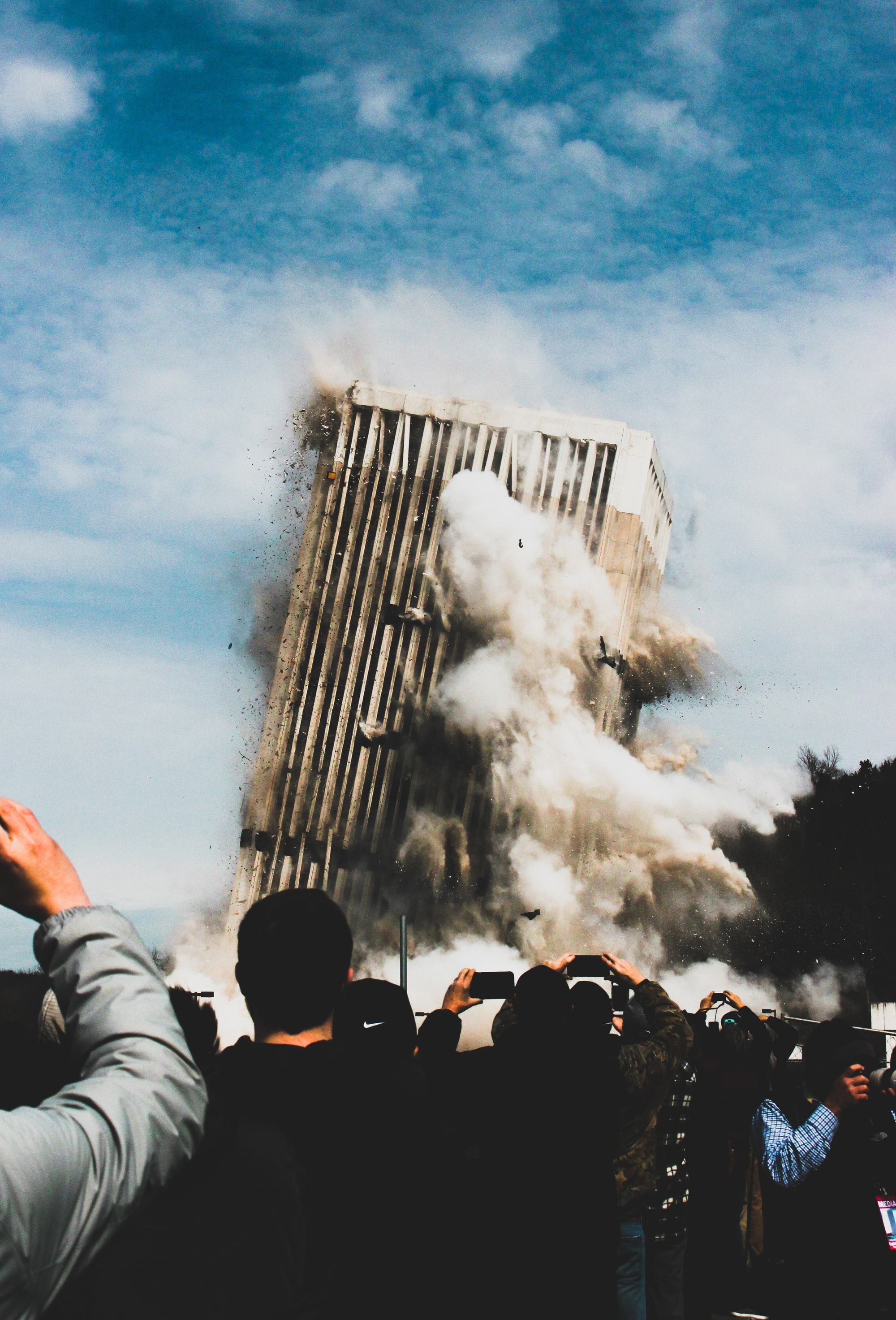 A group of people watch and record a building being imploded.