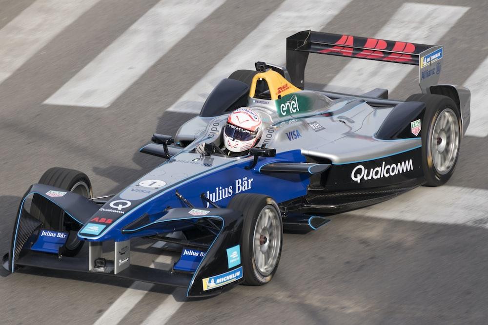 man ridding blue racing car on road