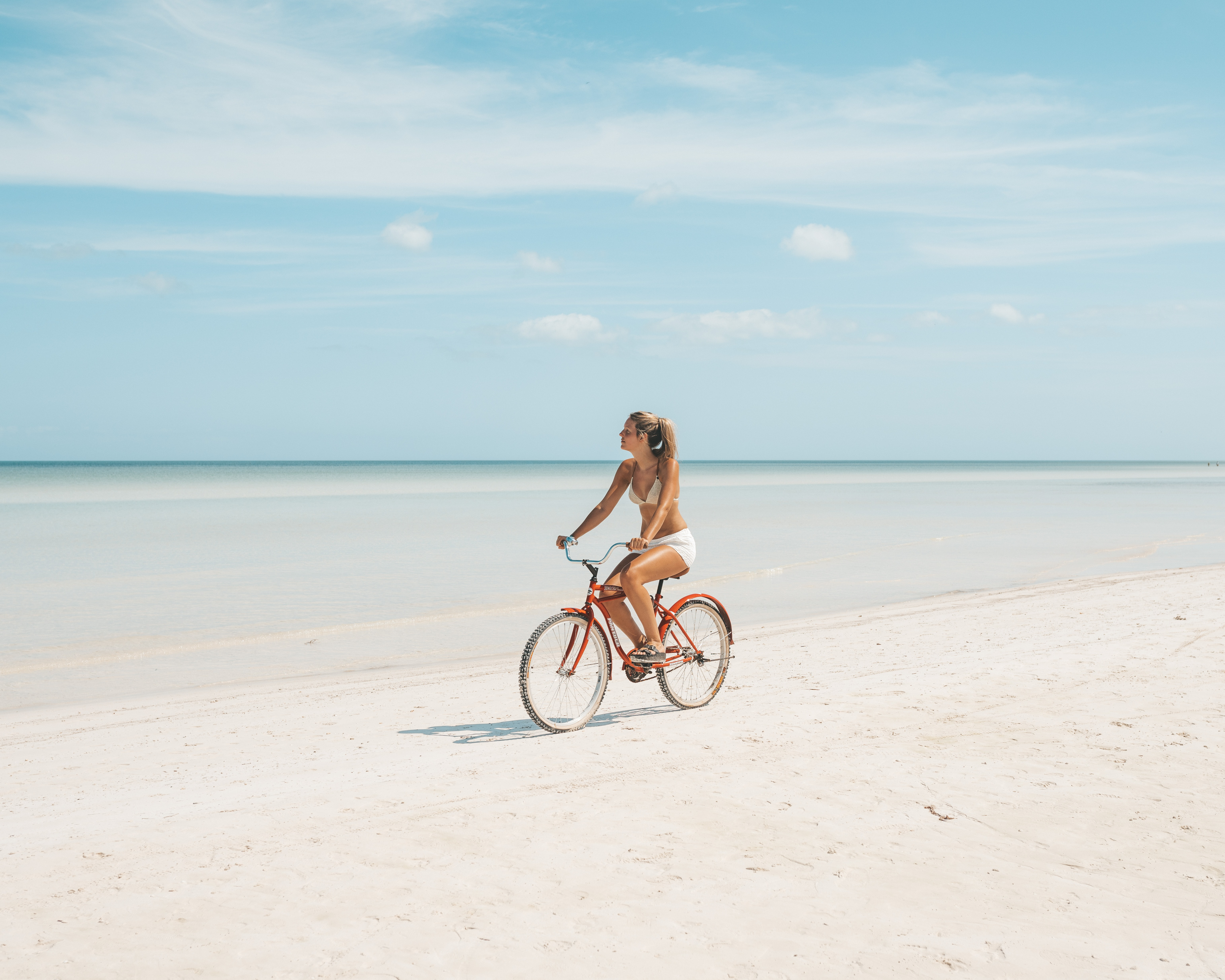 woman riding on bicycle near seashore during daytime