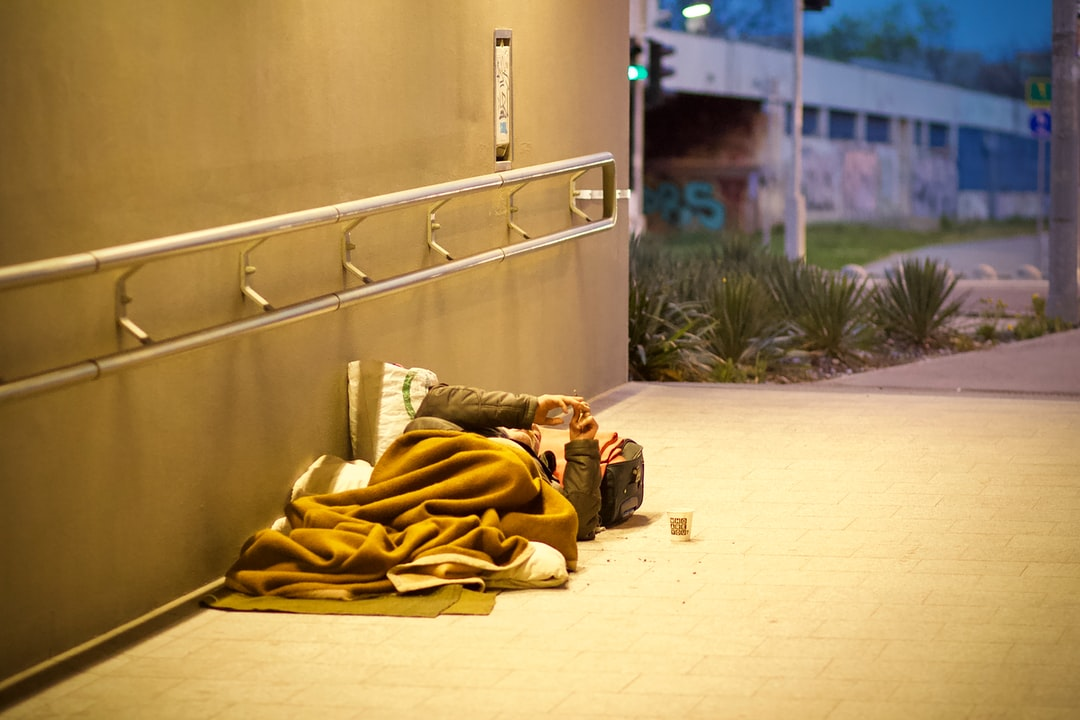 """During my regular walk back home I went by this poor guy lying on the street smoking a cigarette. He had this """"cozy"""" living room, an underground tunnel with a nice view to the other side of the street. He might have his own joke to the world, look at his cup, it says: """"Who are you?""""."""