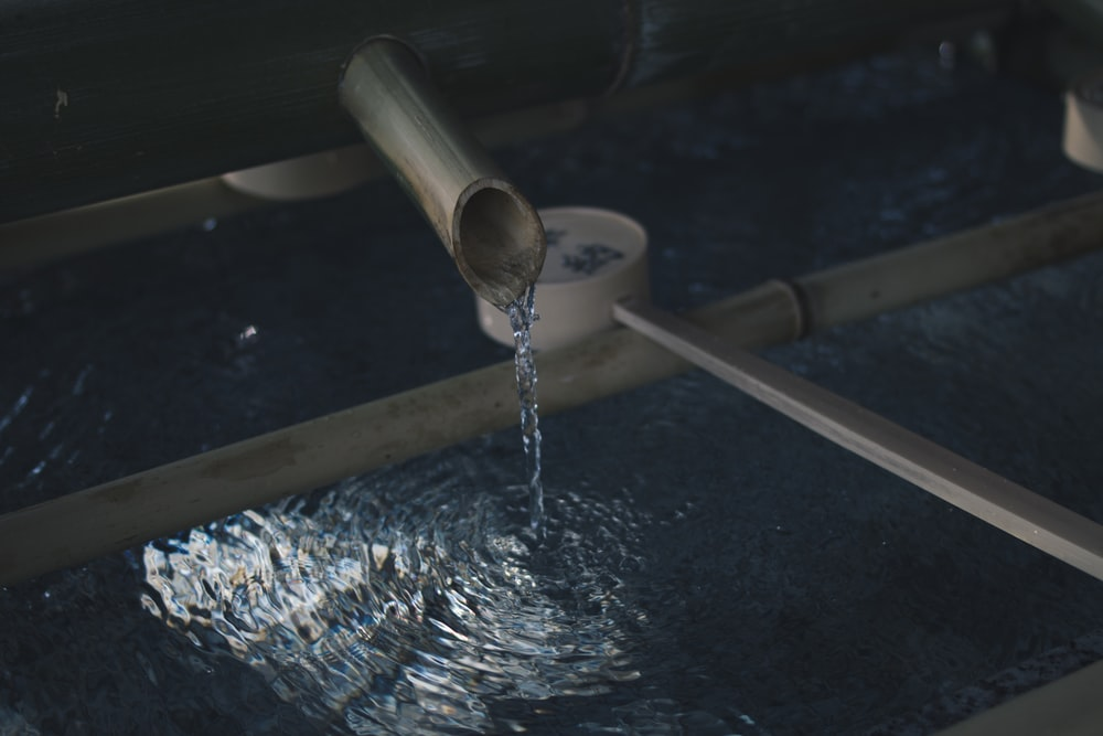 water flowing through brown wooden pipe into surface