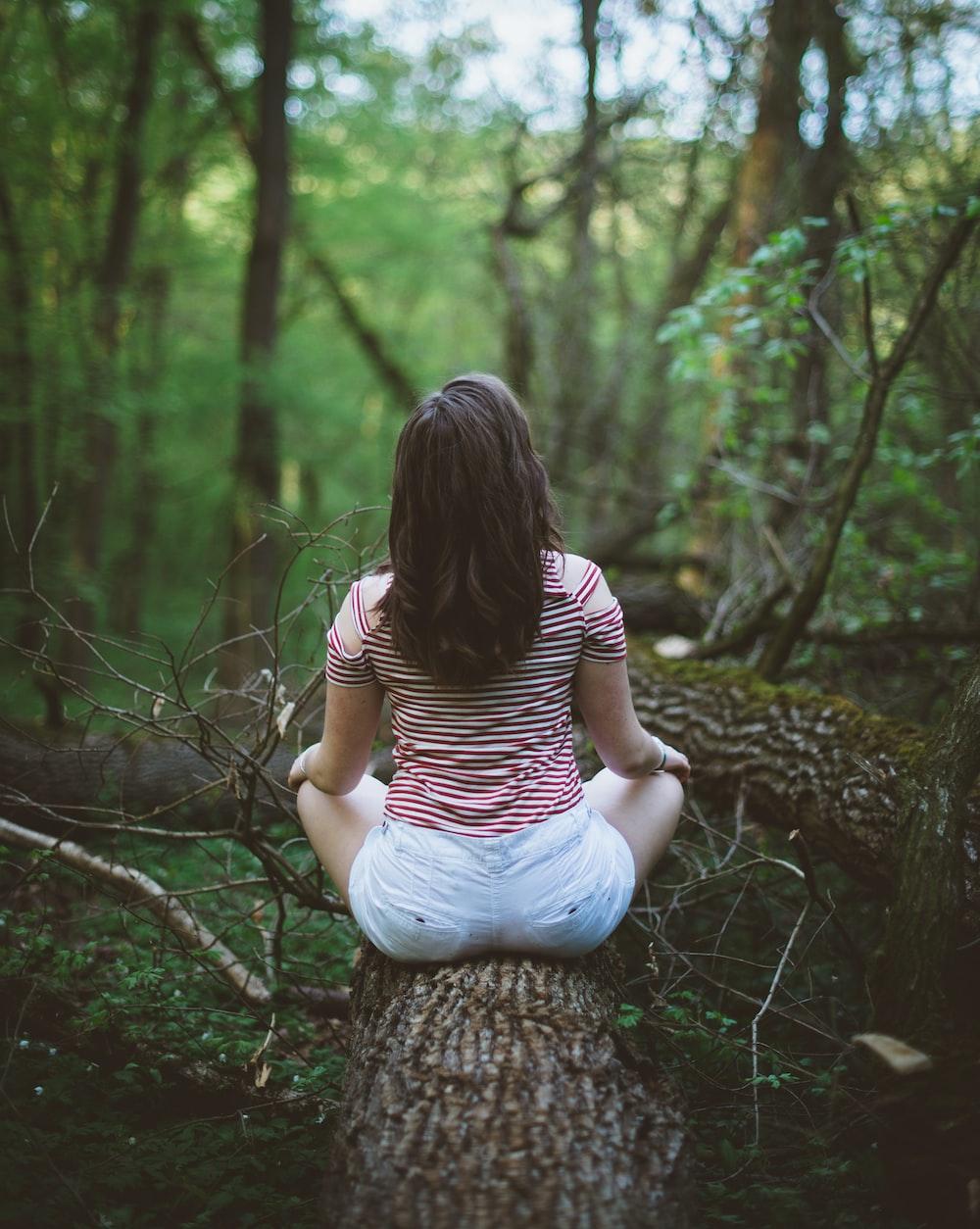 woman sitting on tree log