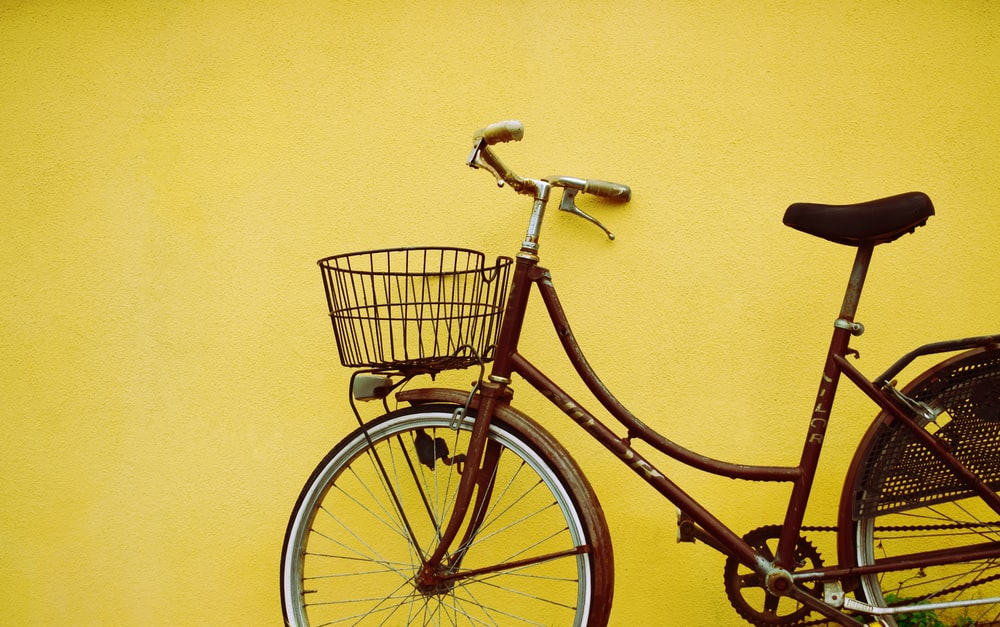 female beach cruiser bike leaning on yellow painted wall