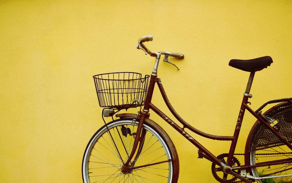 female beach cruiser bike leaning on yellow painted wall