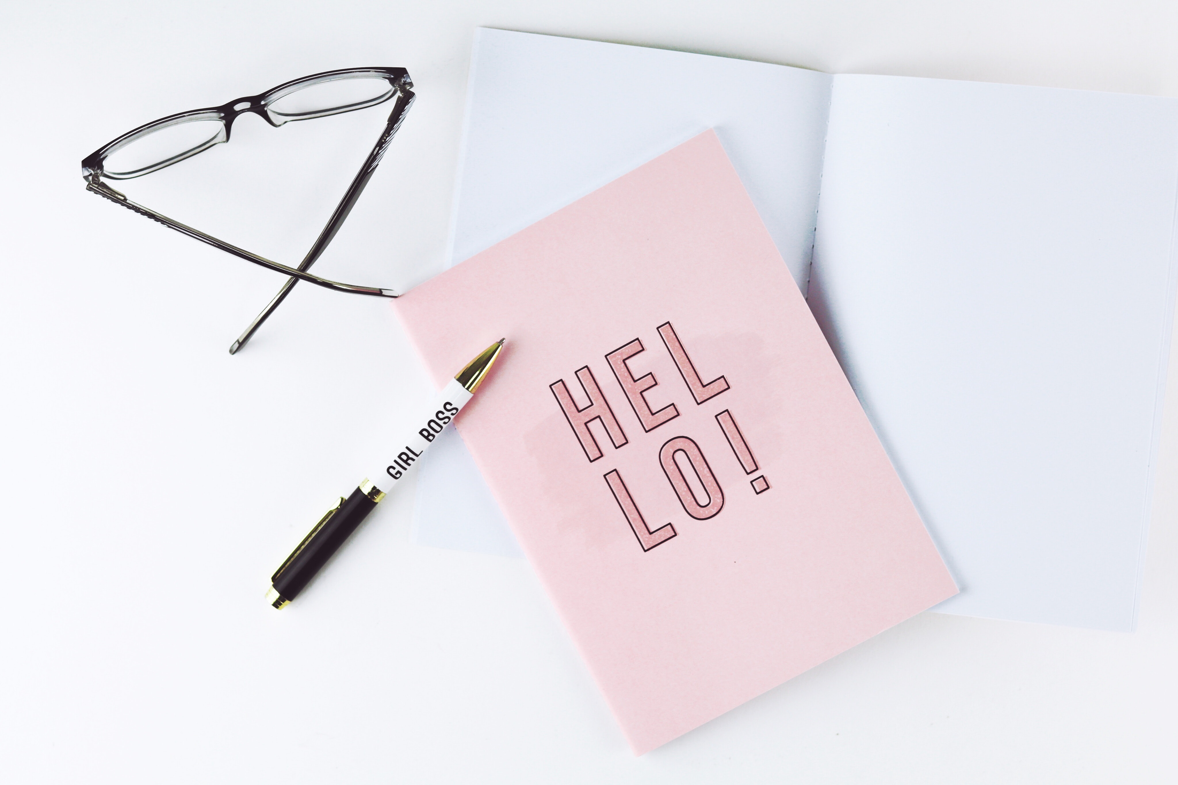 black ballpoint pen beside pink paper with hello written