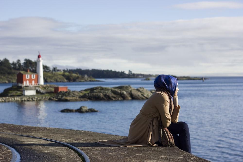 woman sitting on dock near lighthouse