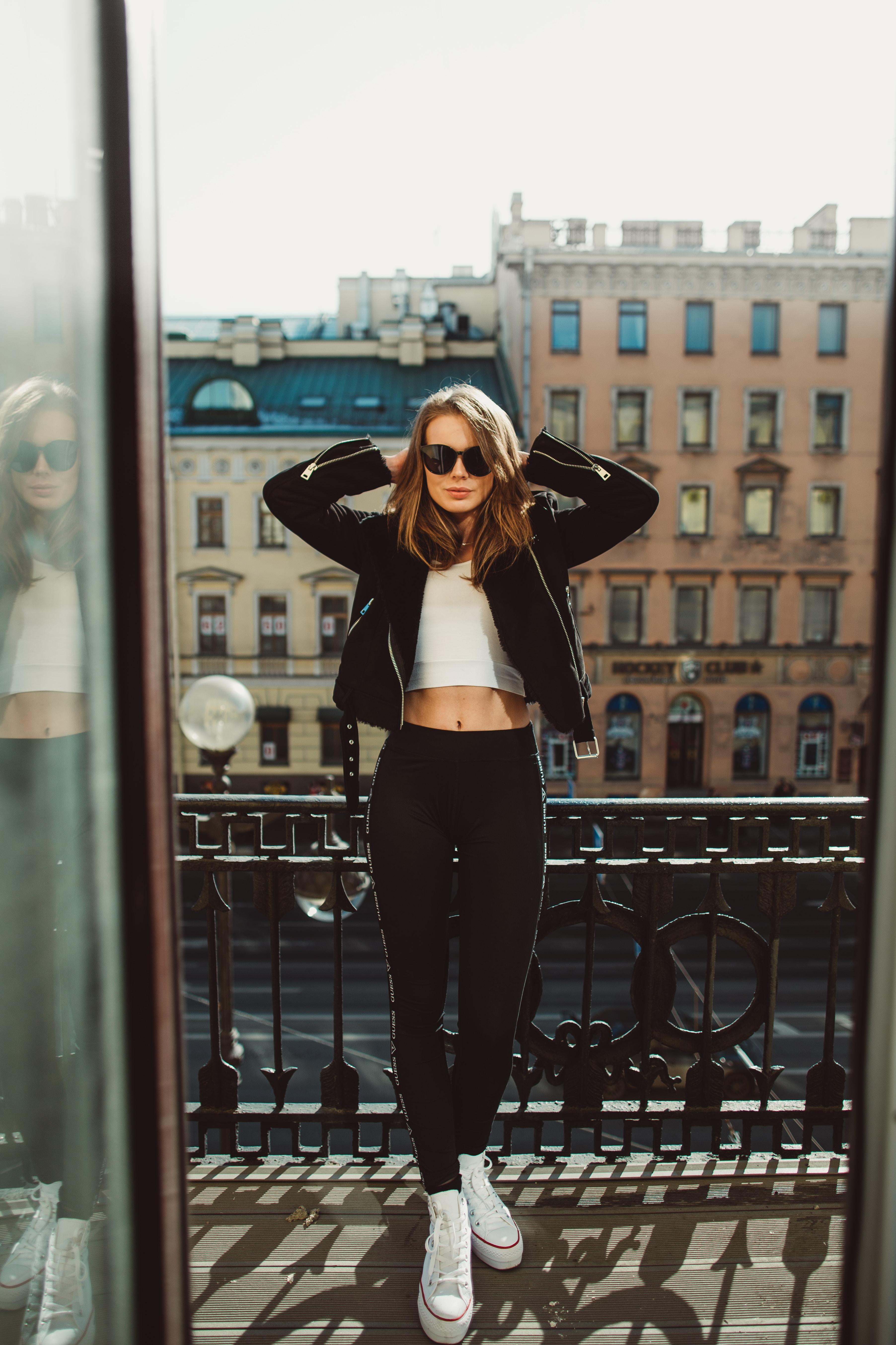 woman standing on balcony leaning on black steel rail