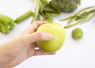 person's hand holding green apple