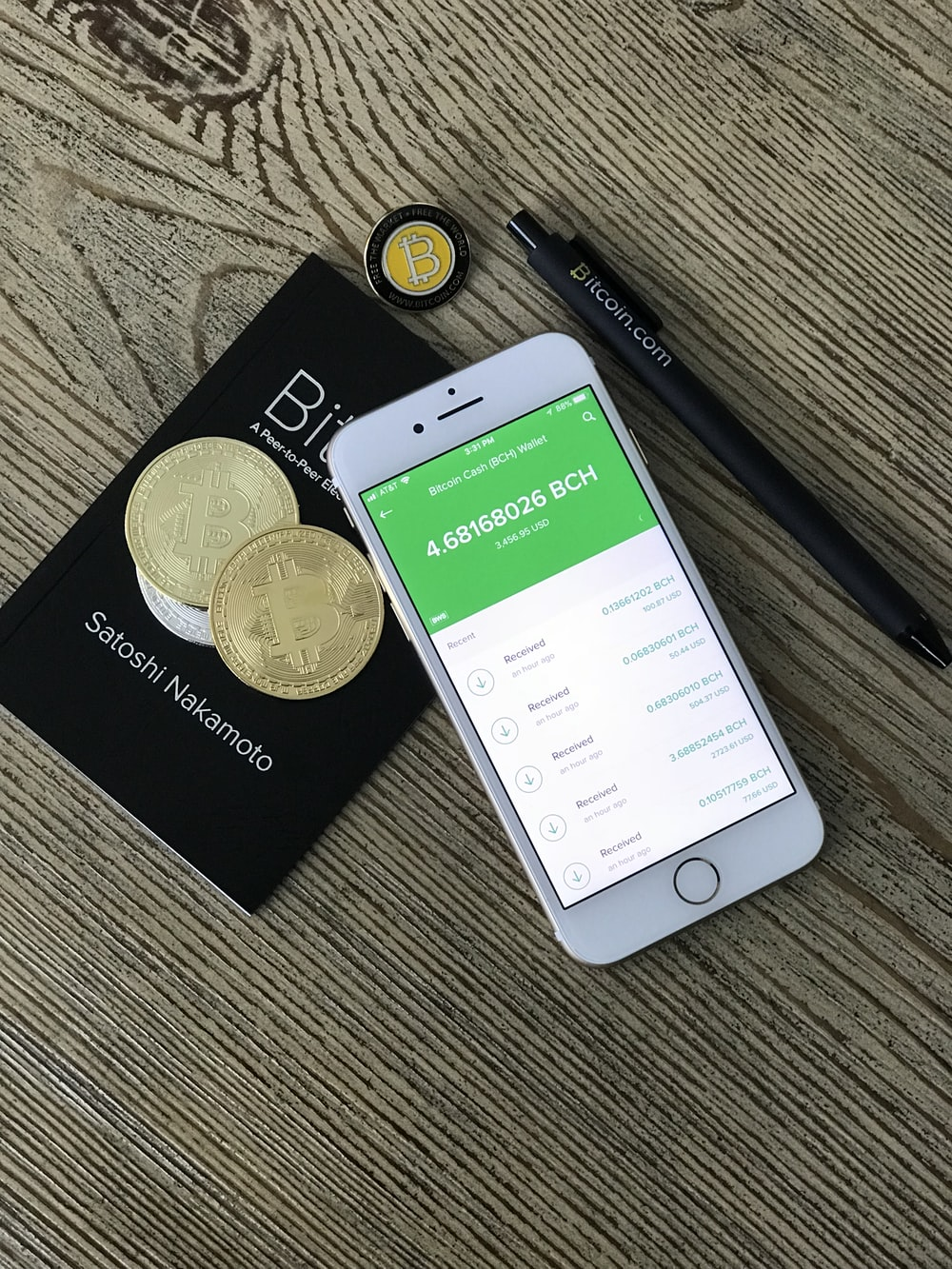 silver iPhone 6 beside two coins